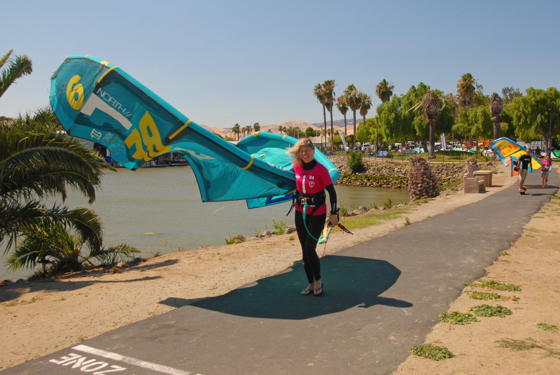 woman walking with kiteboard kite under her arm