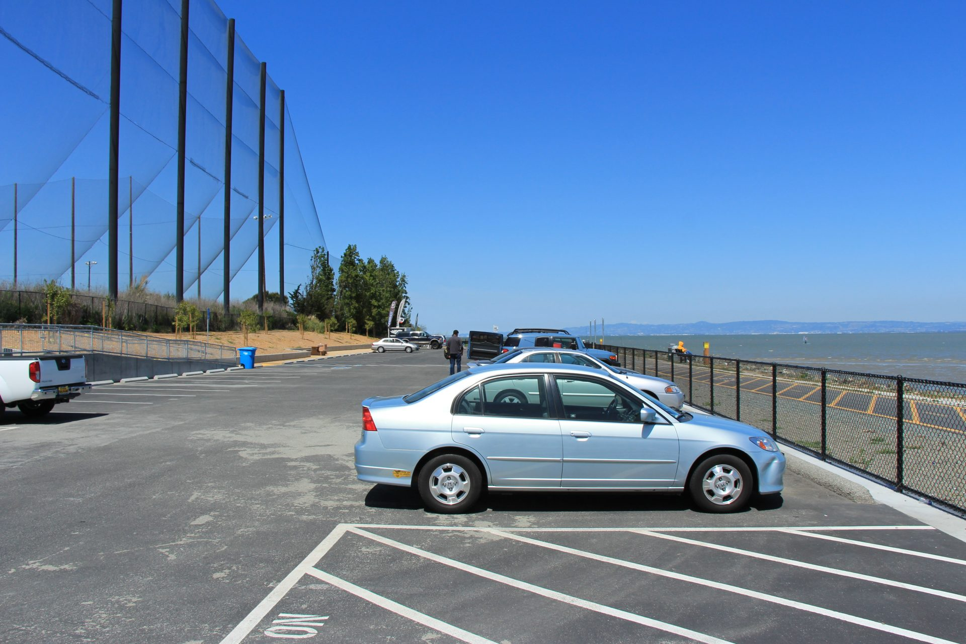 Parking lot with driving range on left and short chainlink fence on right