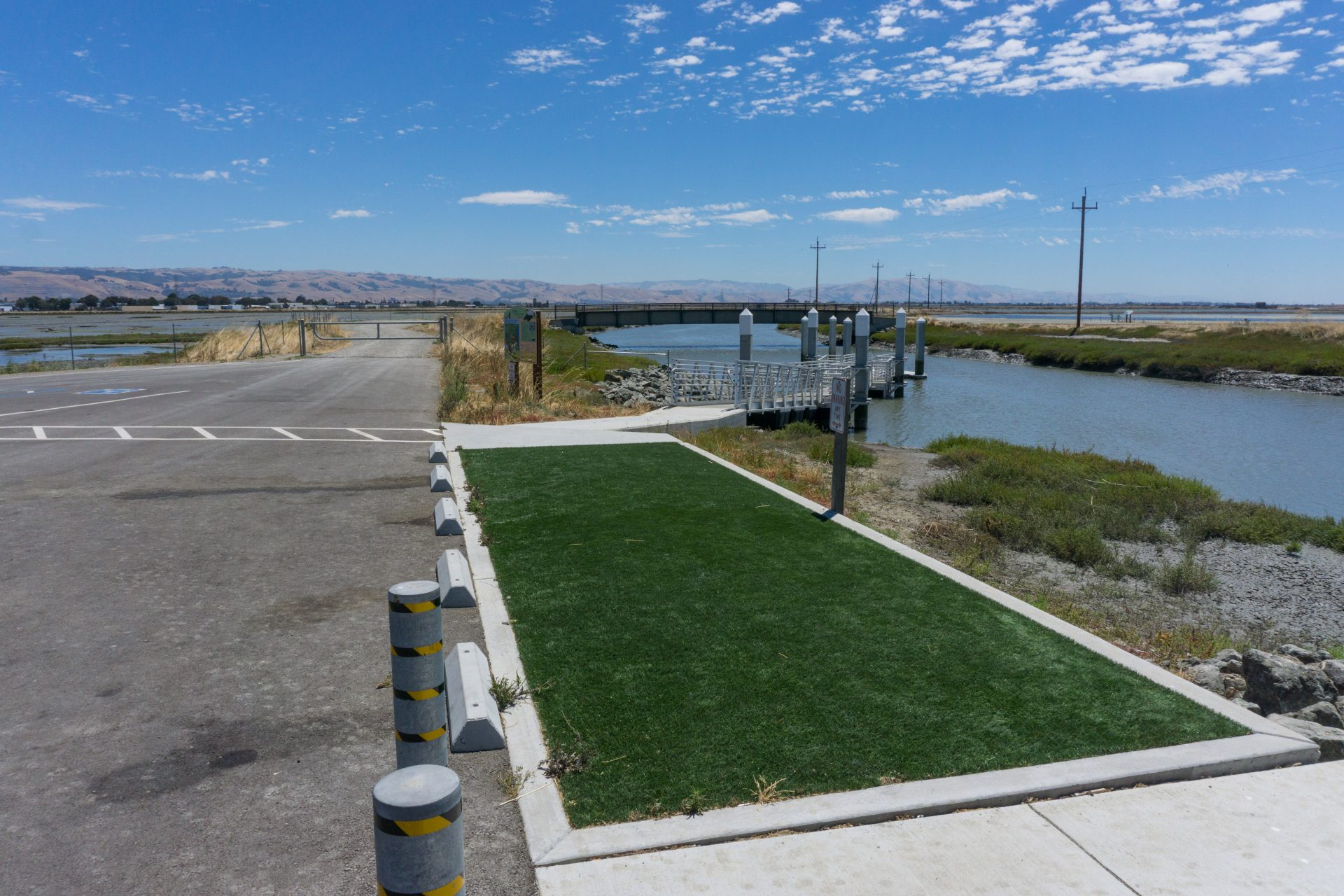 flat area covered in astroturf with parking lot on left and dock on right