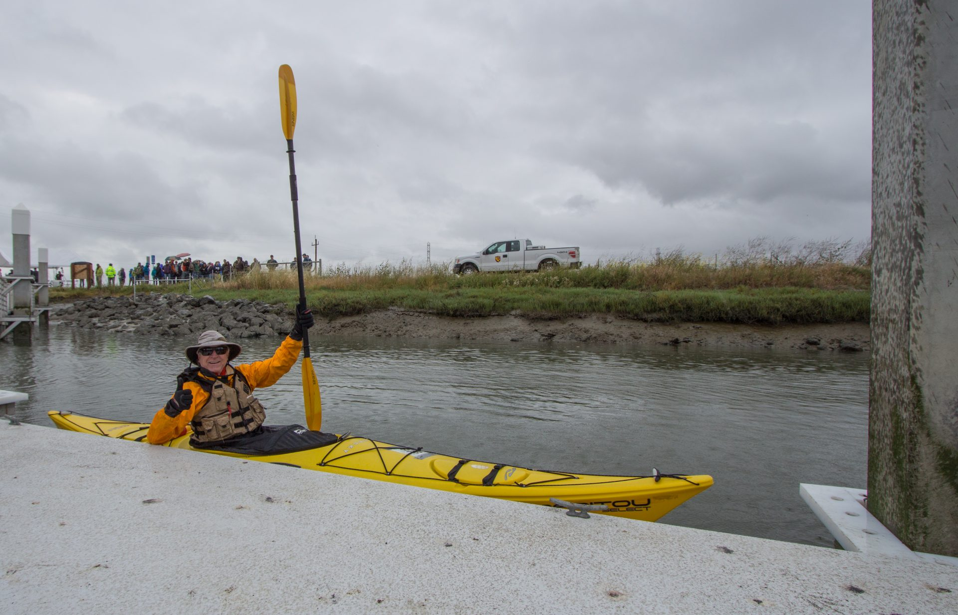 Person in yellow kayak in water alongside dock, waving and holding up paddle