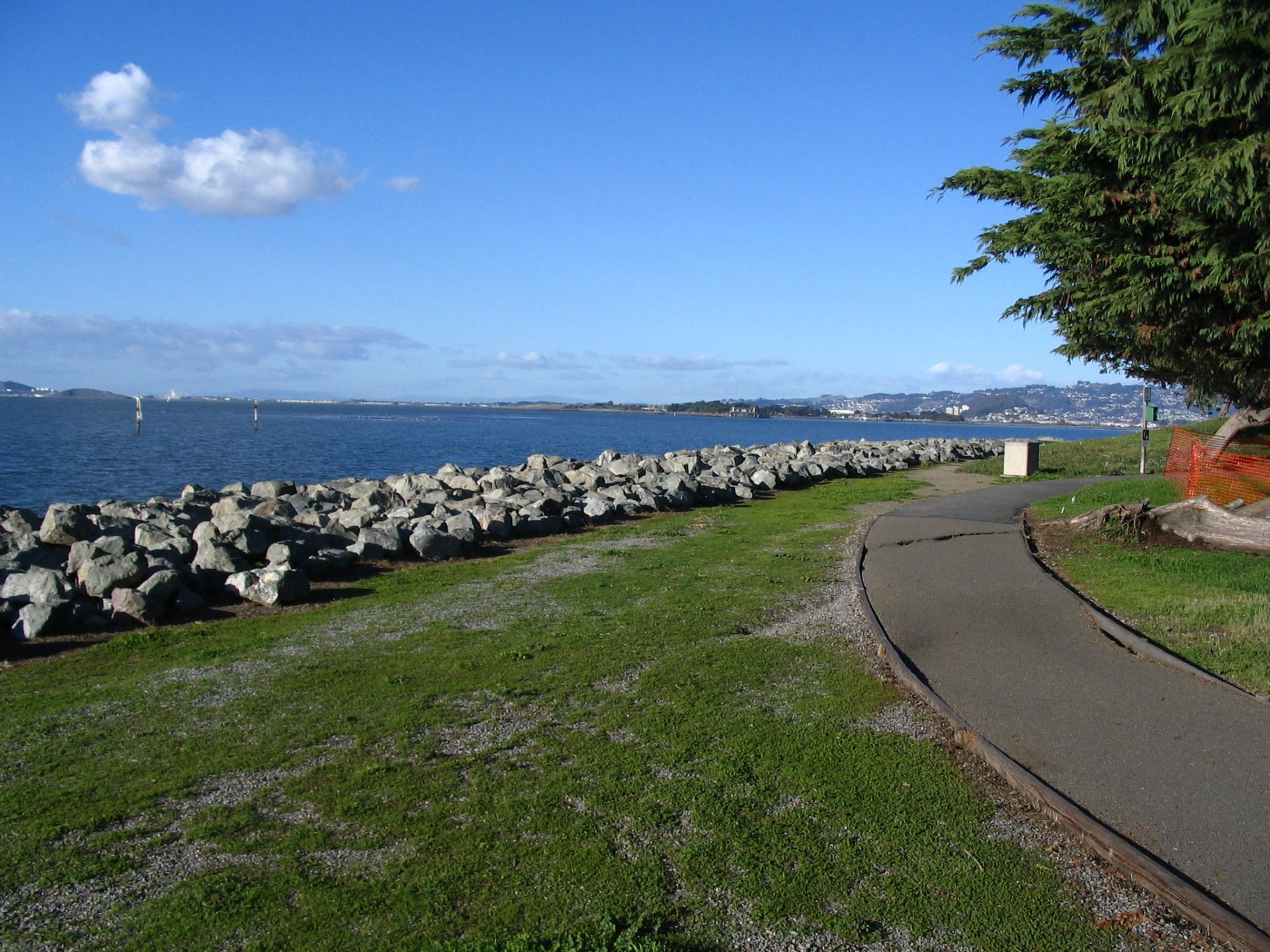 Blue sky and water, riprap, green grass, and curving paved path