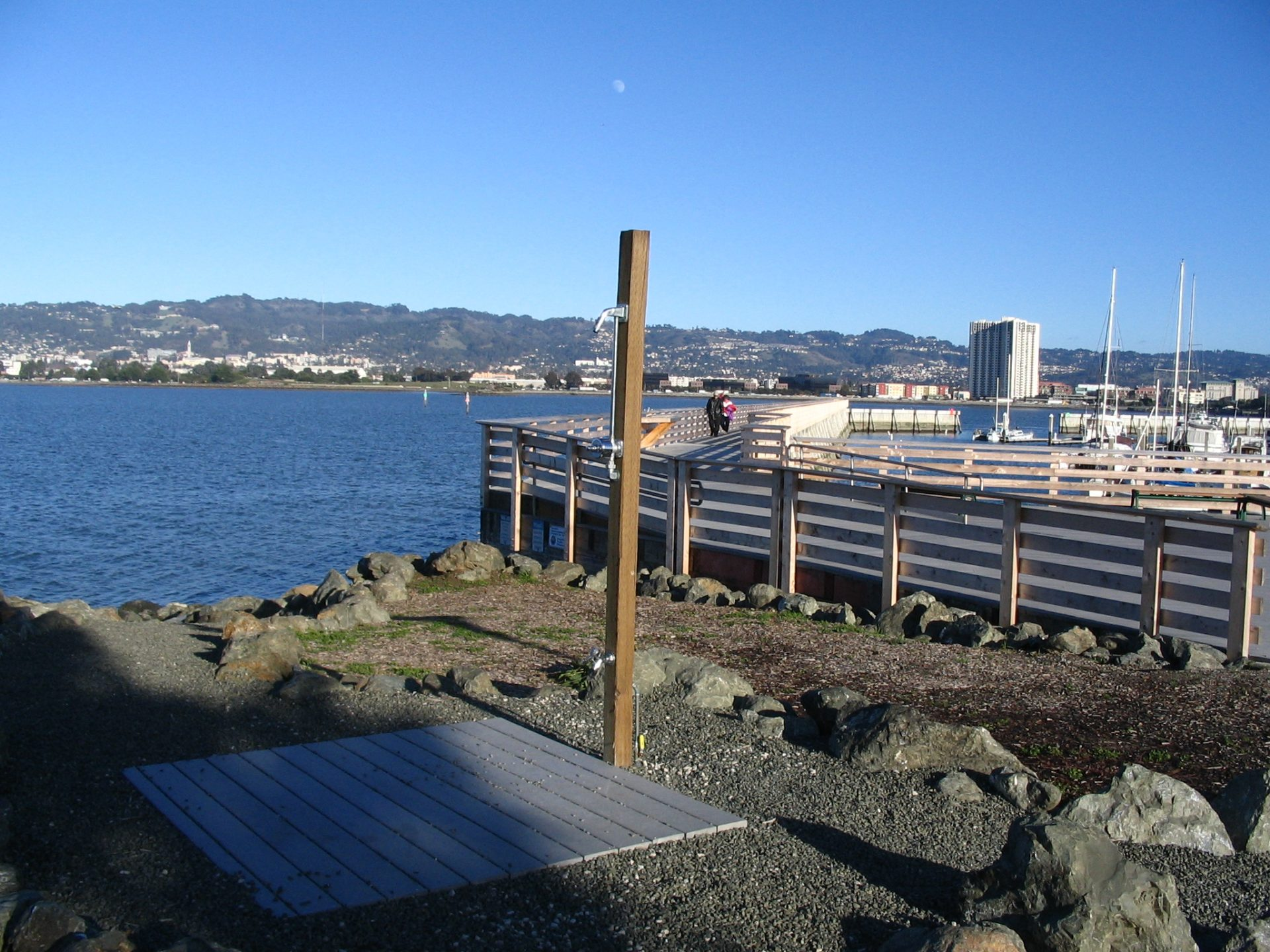 outdoor shower with plank floor, and wooden pier in background