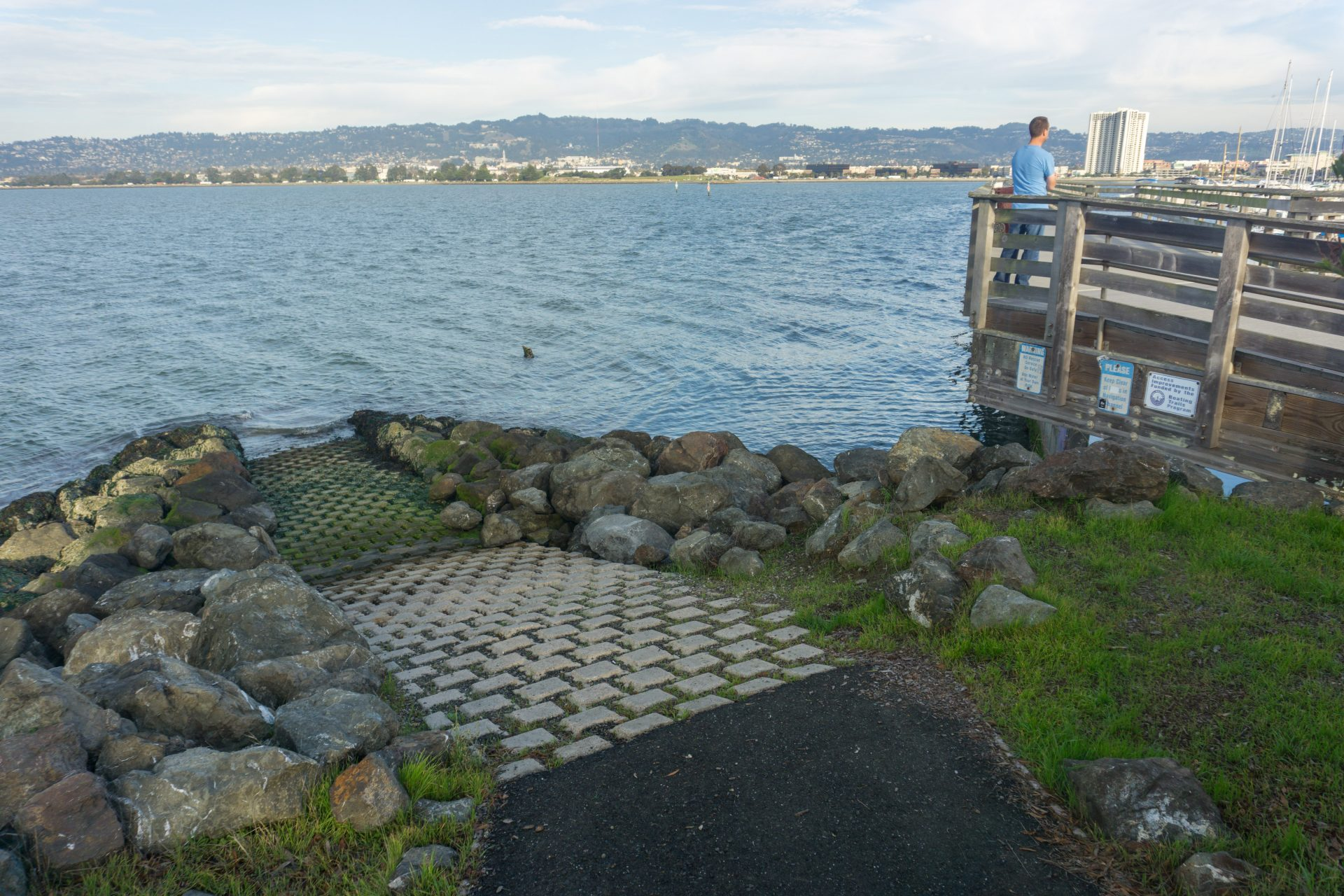 riprap on either side of cobblestone ramp into water, with wooden observation deck on right