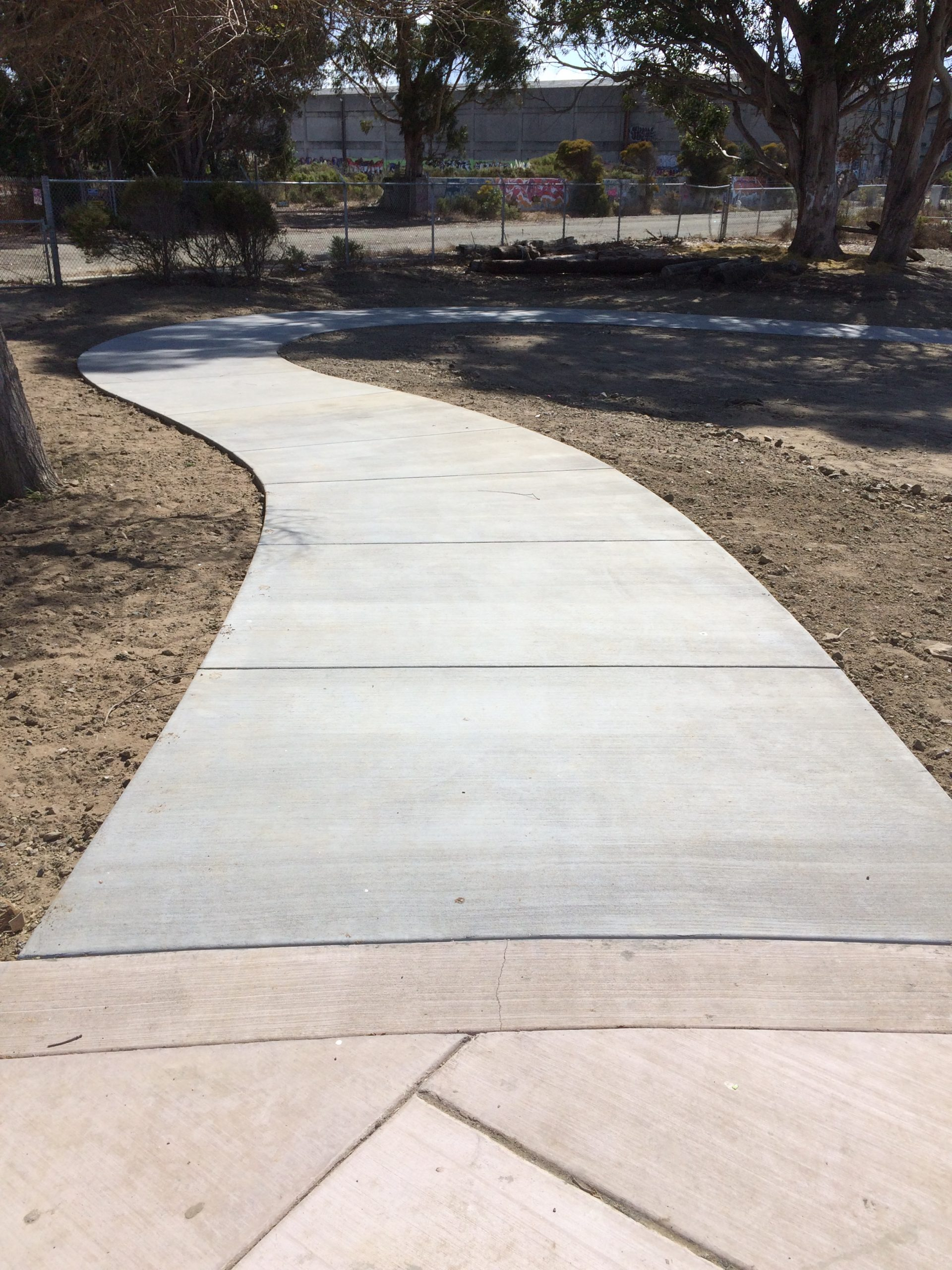 New-looking concrete path curves left and then right through bare dirt