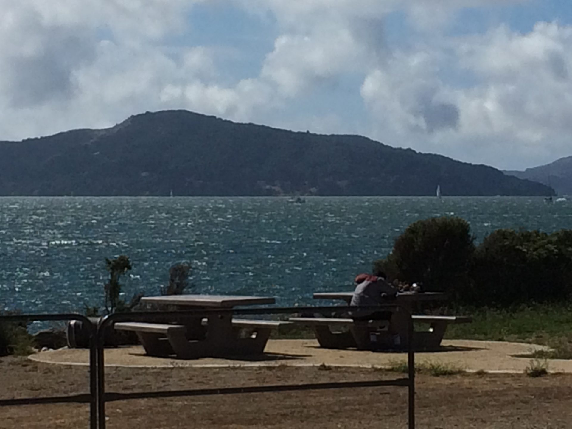 person with head down on concrete picnic table, next to another empty table, Mount Tamalpais in distance