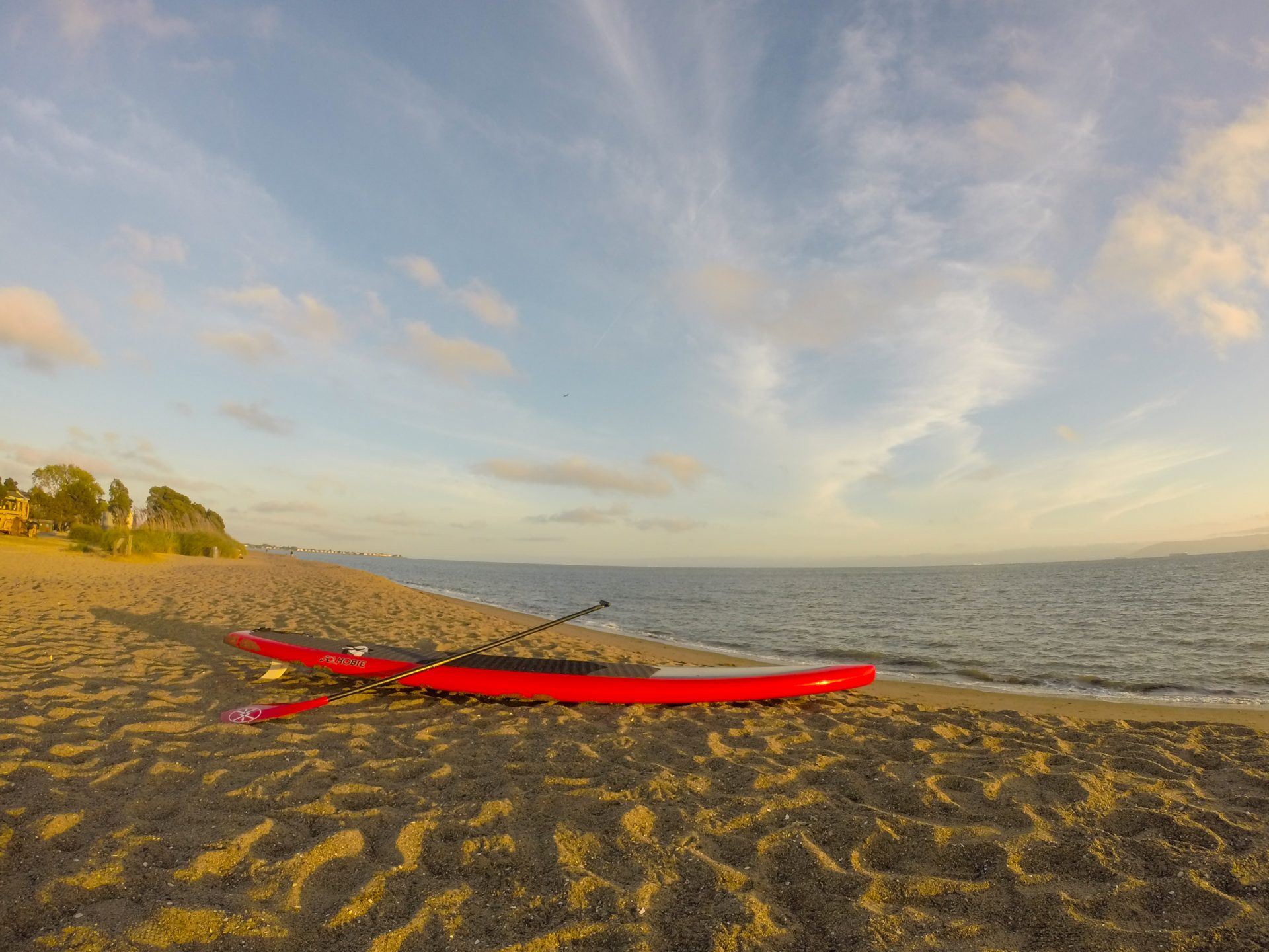 Red and black paddleboard on sandy beach