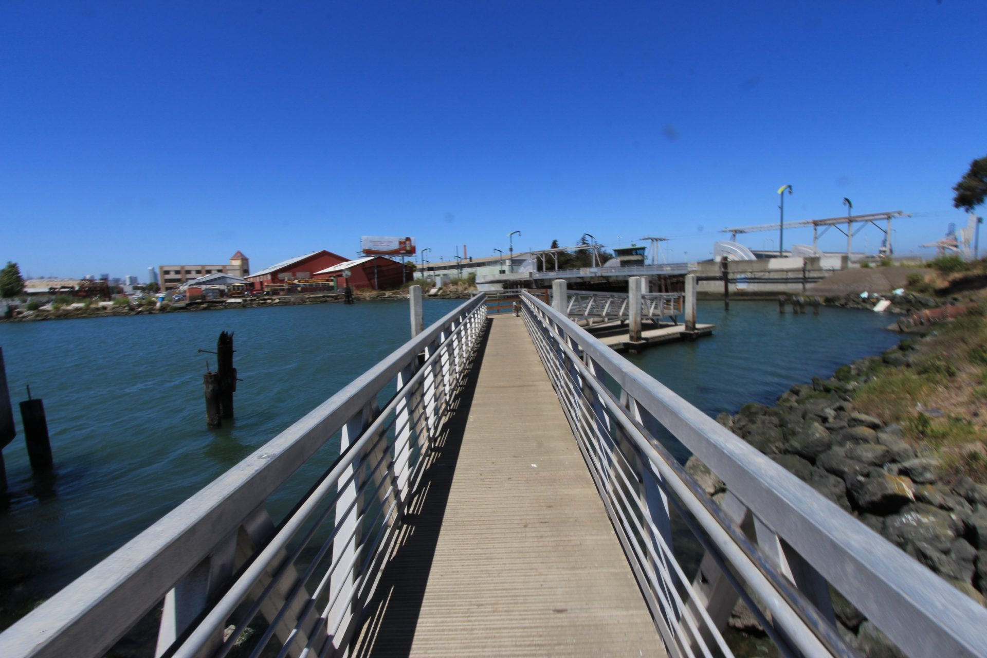 Long walkway with railings, from shore to dock