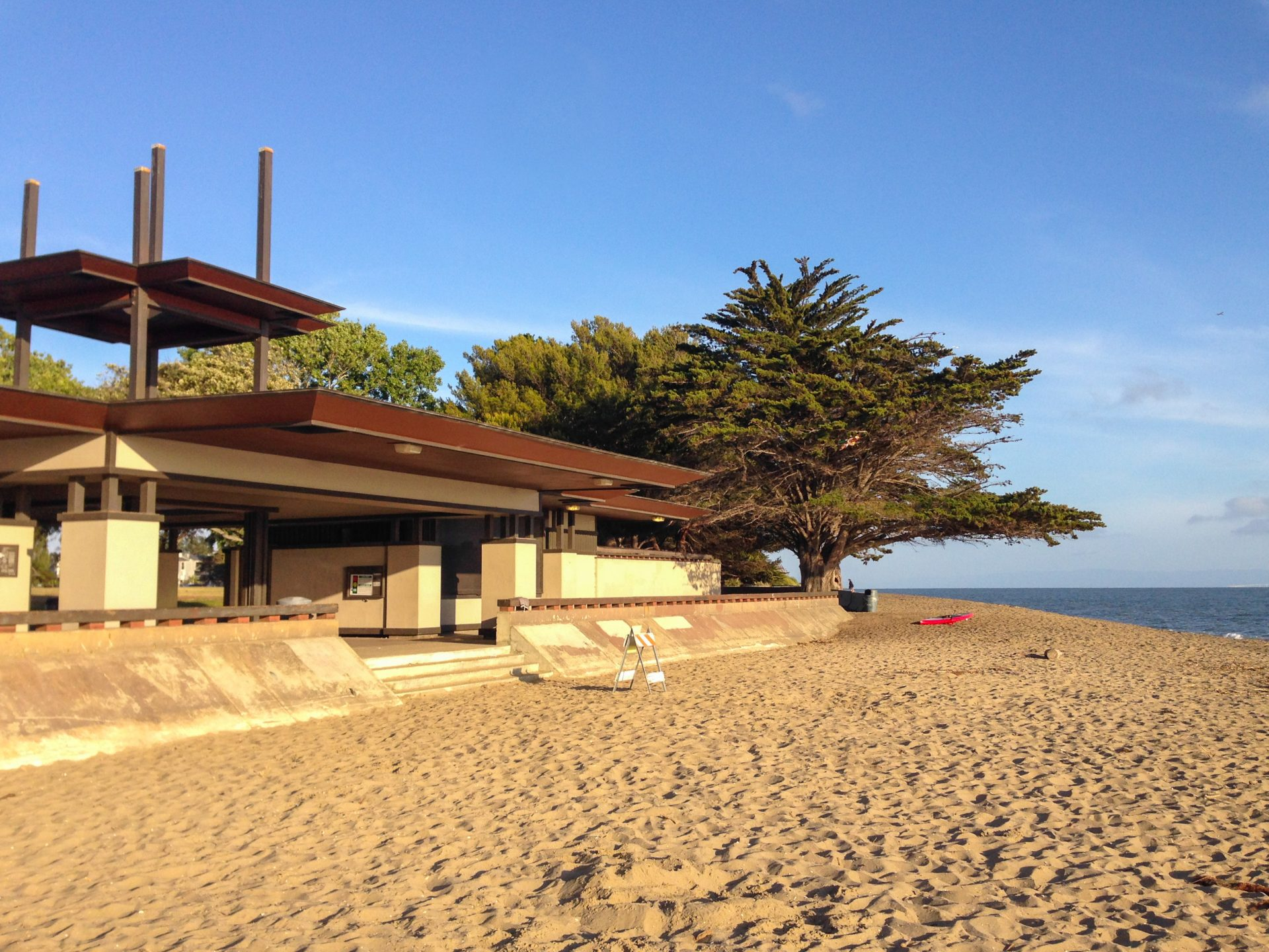Wide sandy beach in evening light, with visitor center on left