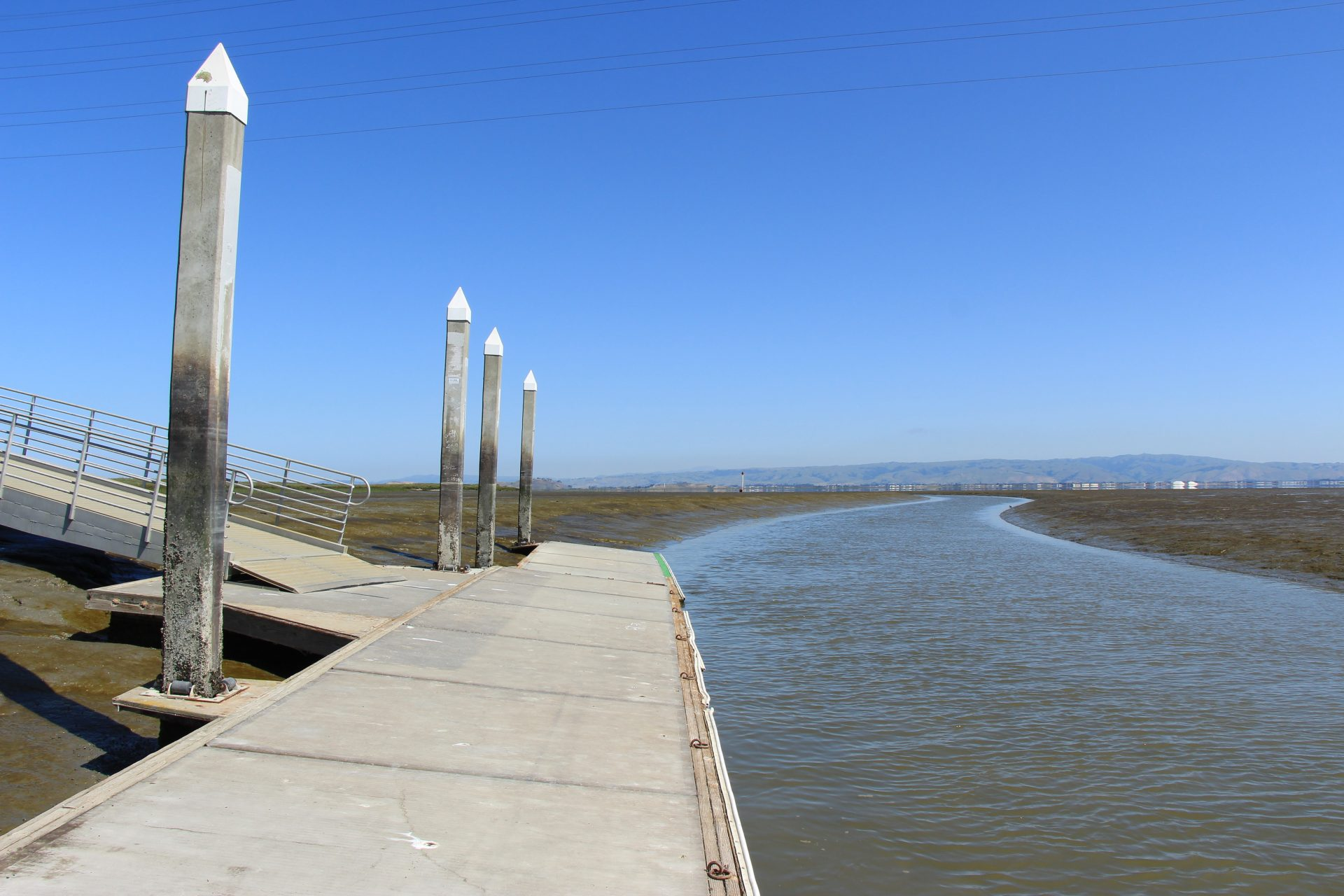 floating dock in a narrow channel with mudflats exposed at low tide
