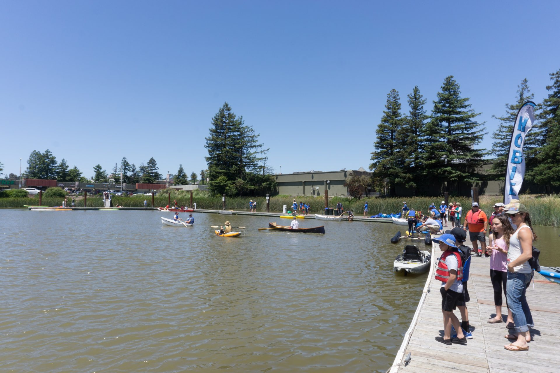 People standing on dock along right, looking out on water with several kayakers