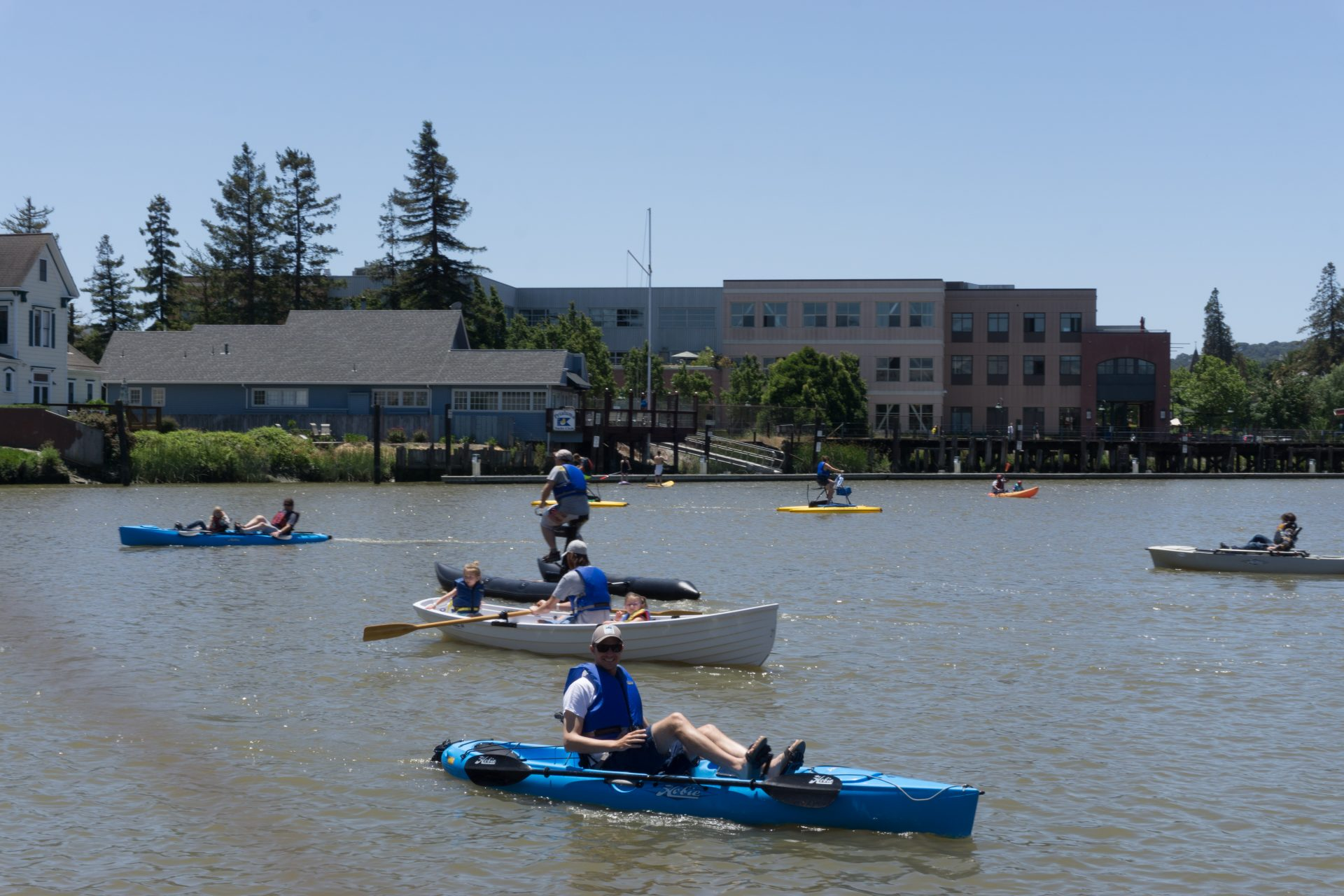 Many kayakers and boaters crossing water in both directions, with buildings in distance