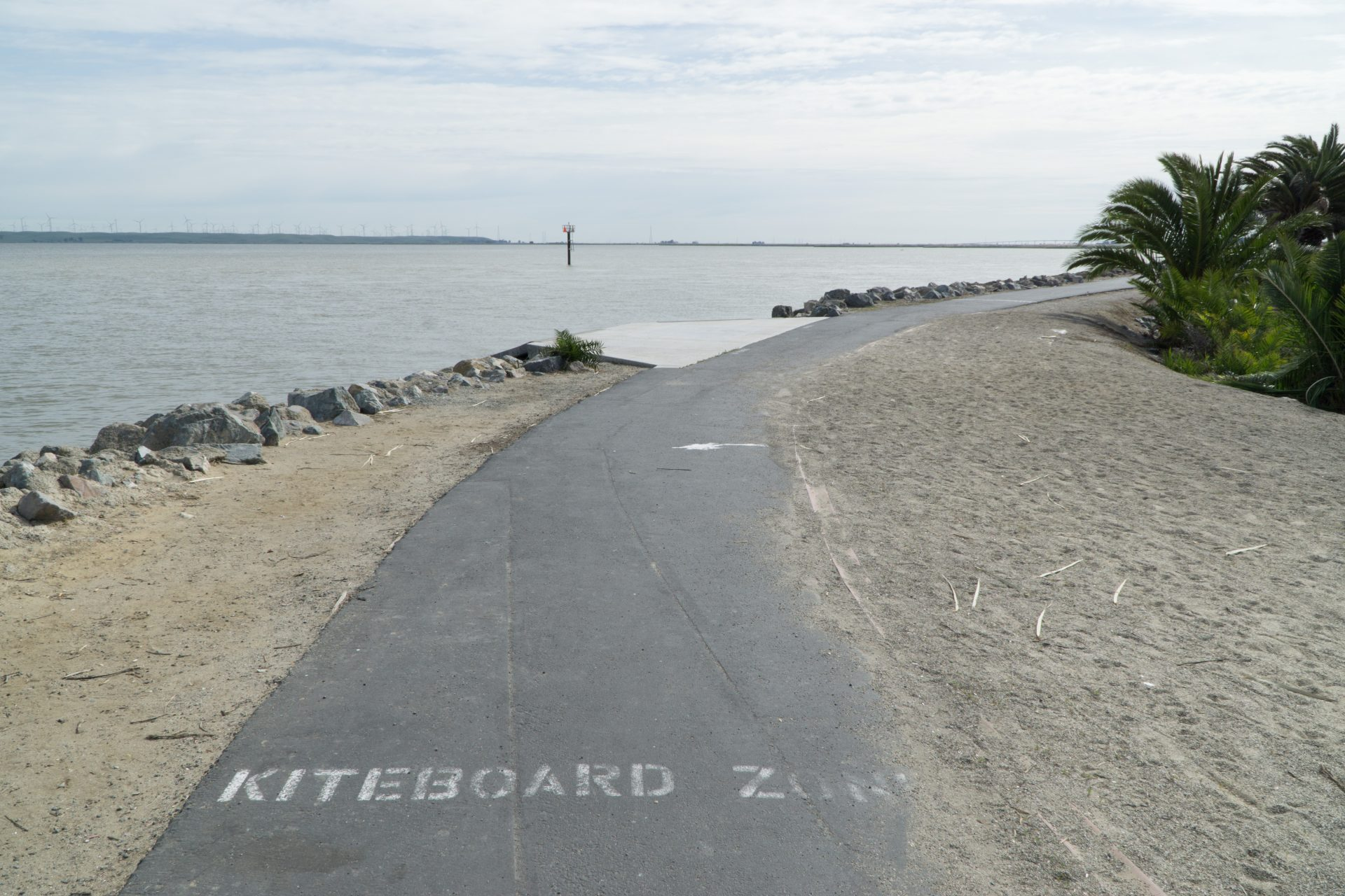 paved path labeled kiteboard zone, water to left