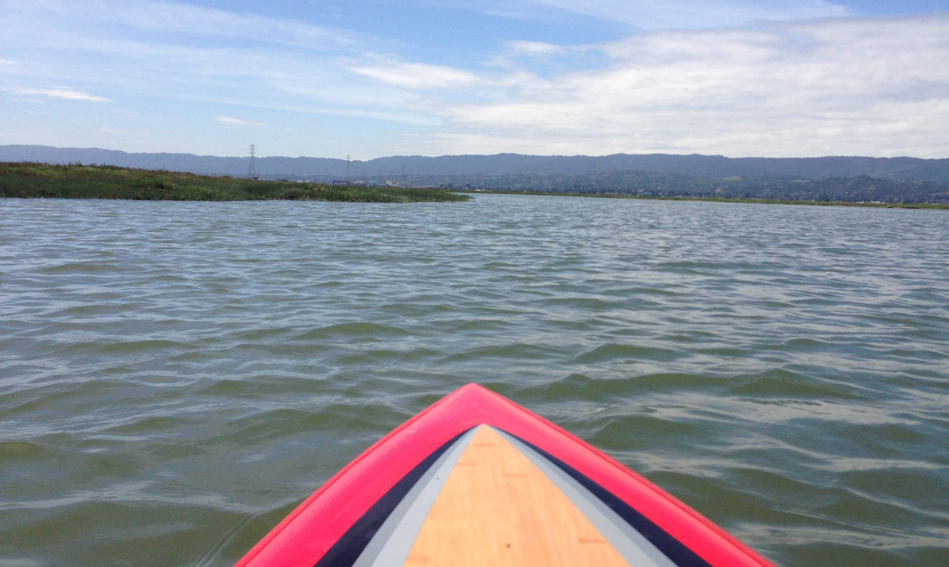 View from paddle board of open water and flat marshlands
