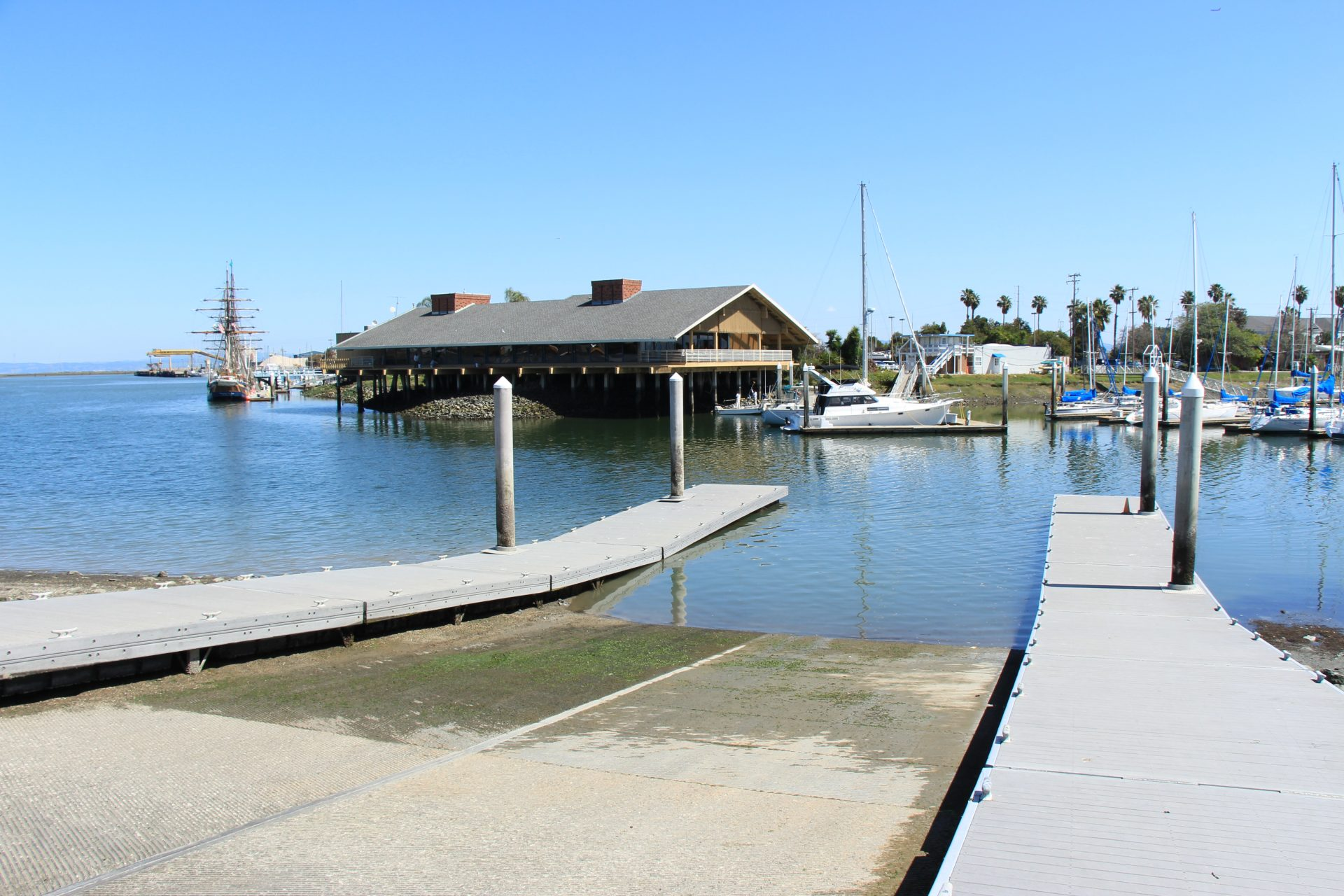 Boat ramp descending into water, with sailboats moored across the channel