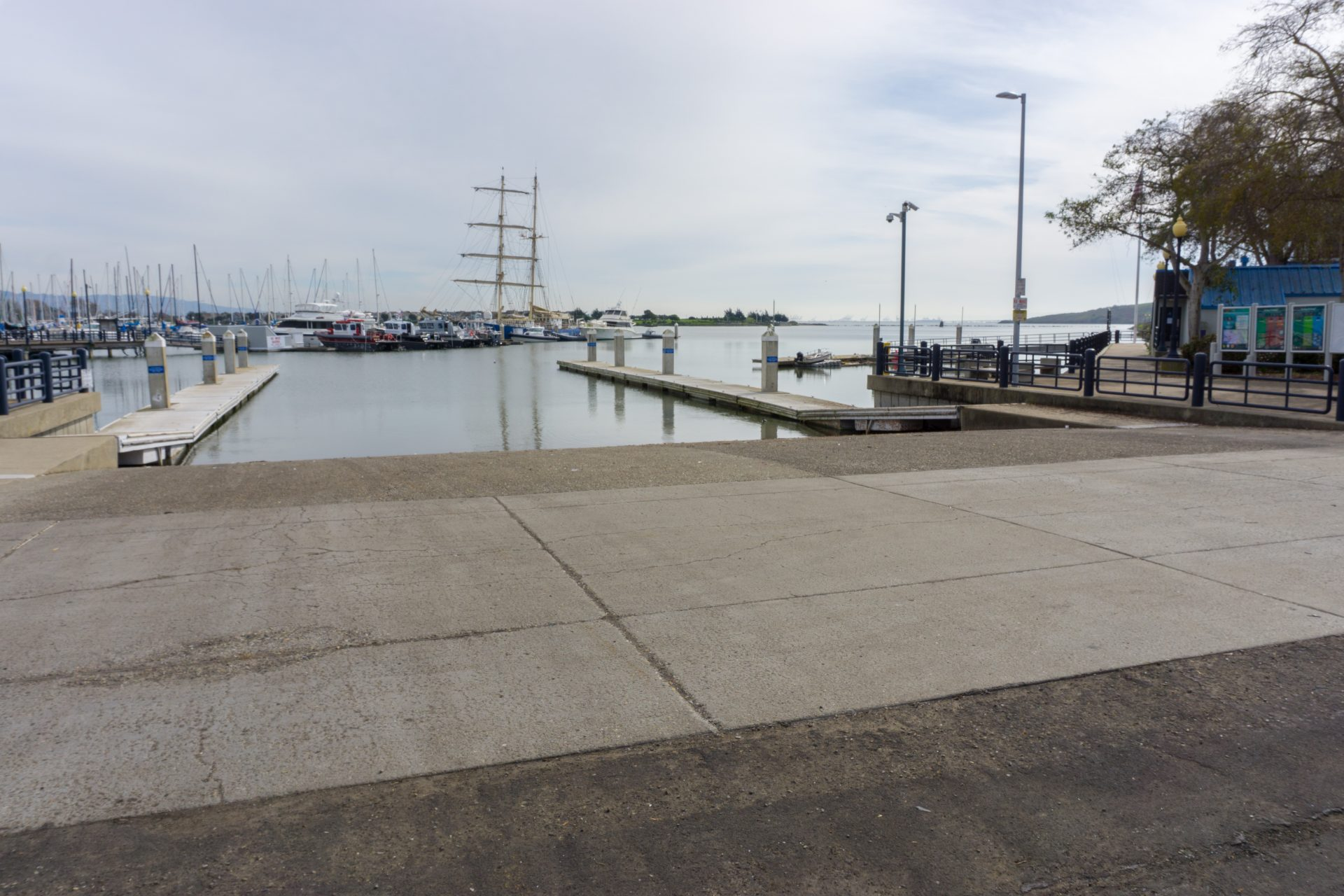 Boat ramp descends into water, marina with boats moored beyond