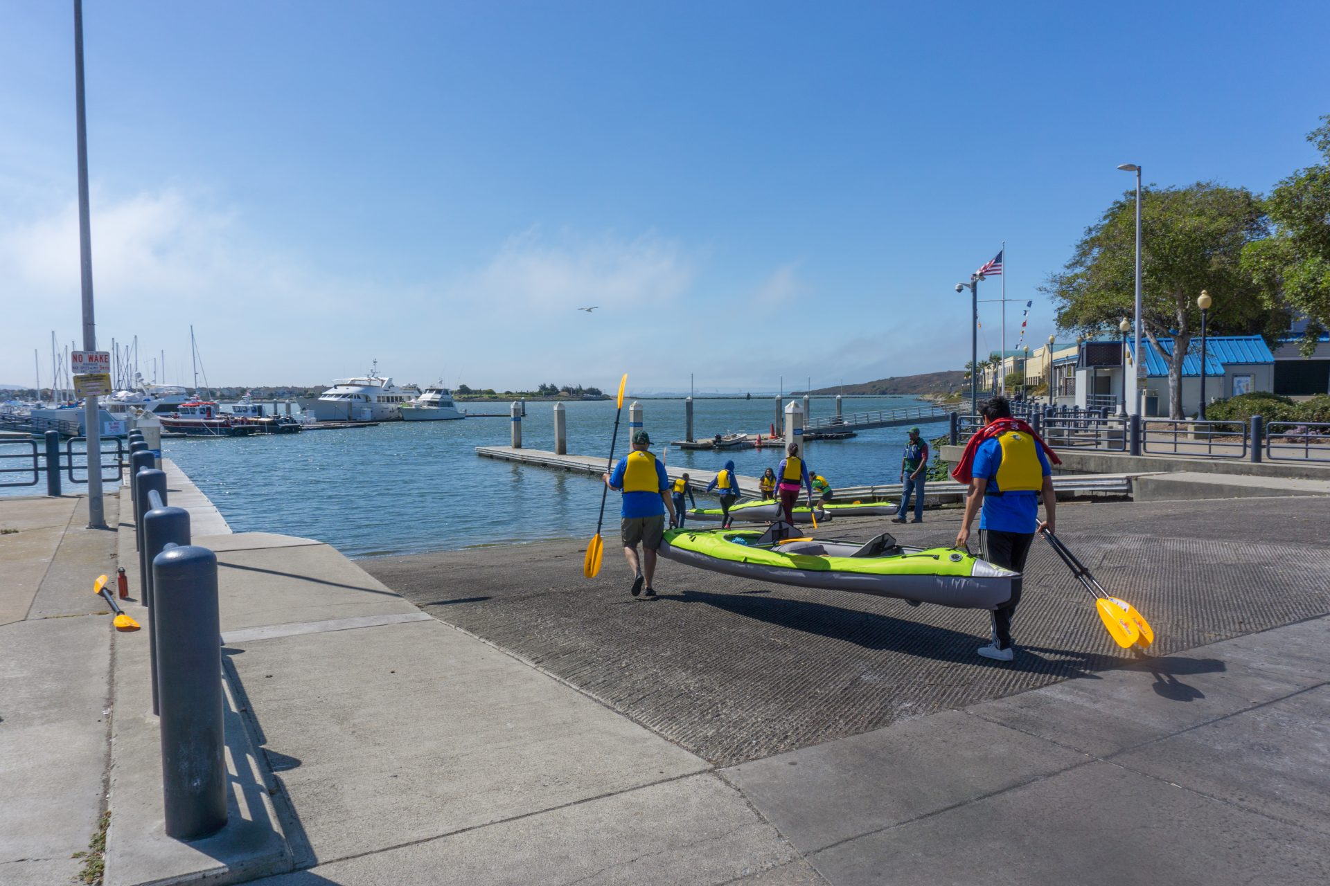 people carrying inflatable kayaks toward water, one holding bow and the other stern