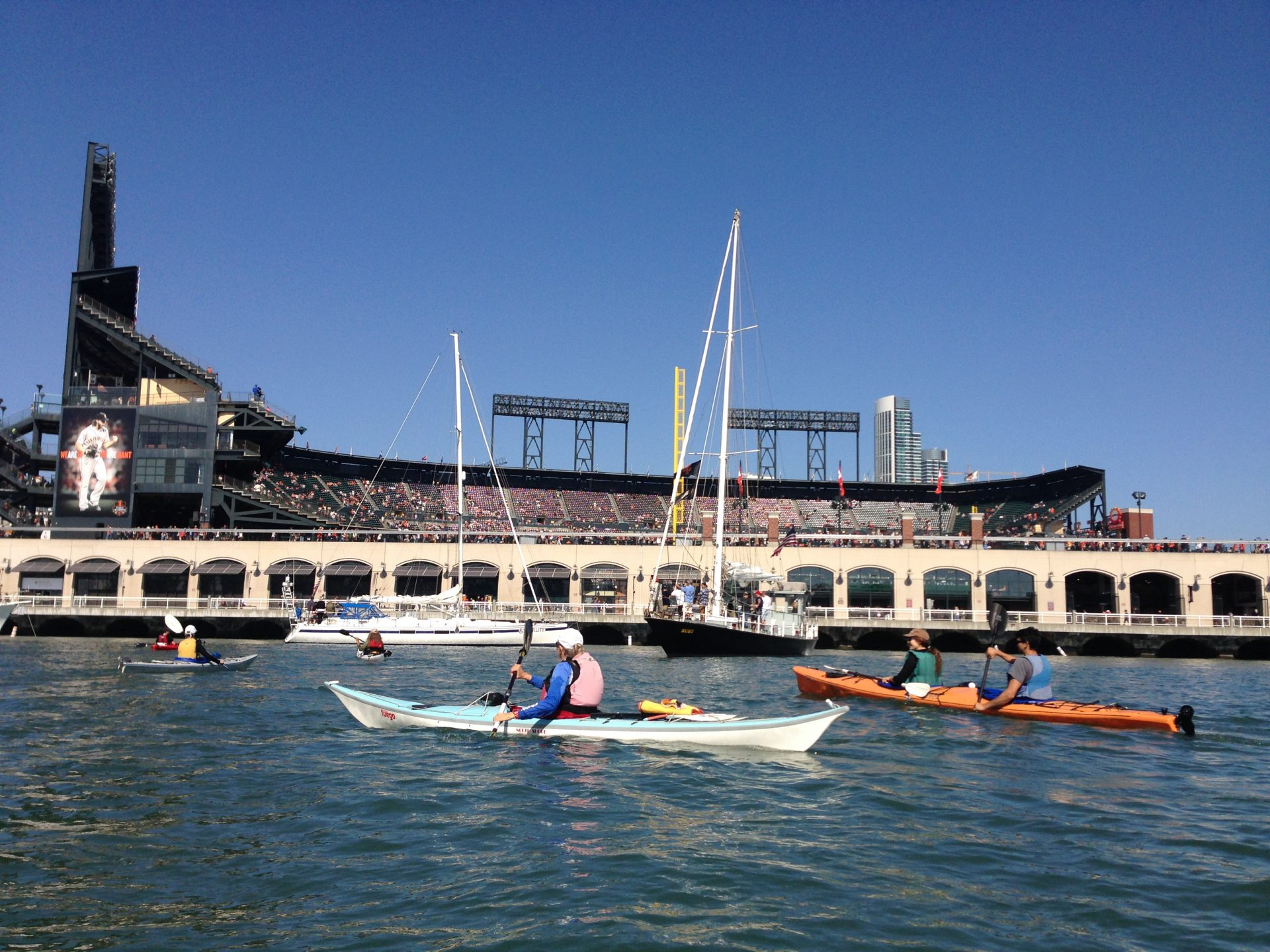 Kayakers and sailboats on the water just outside the Giant's Stadium