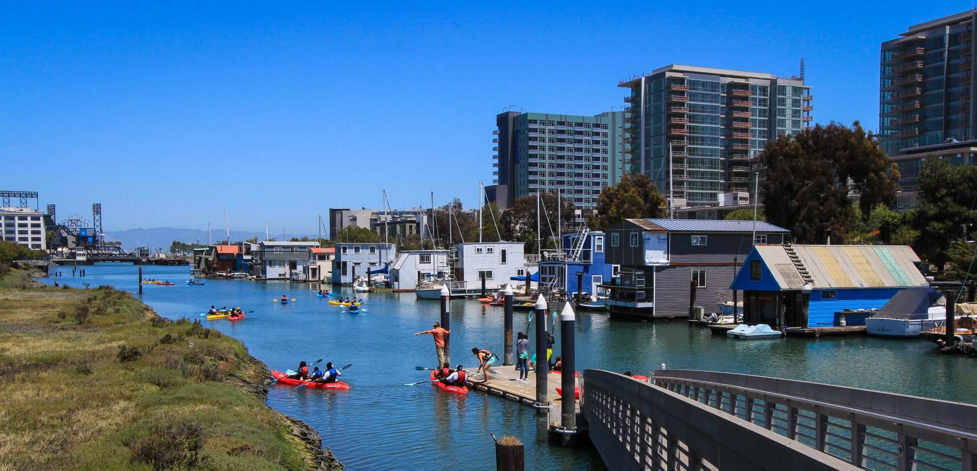 Narrow channel with many color kayaks, and grassy meadow on left and houseboats on right. A ramp descends to a floating dock with 4 people standing on it