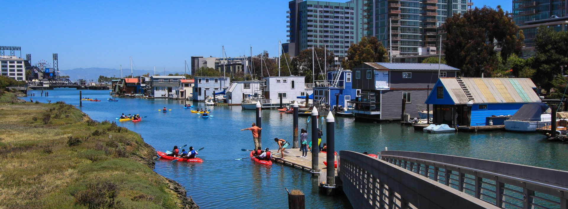green grasses on left, many kayaks in narrow channel, and houseboats along right side