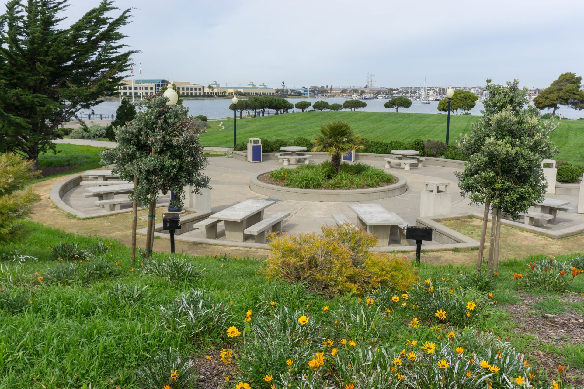 View of flowers surrounding circle of large concrete picnic benches