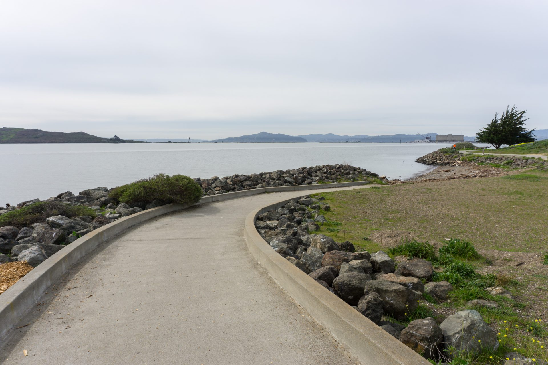 Paved path curves to right, ending at sandy bech