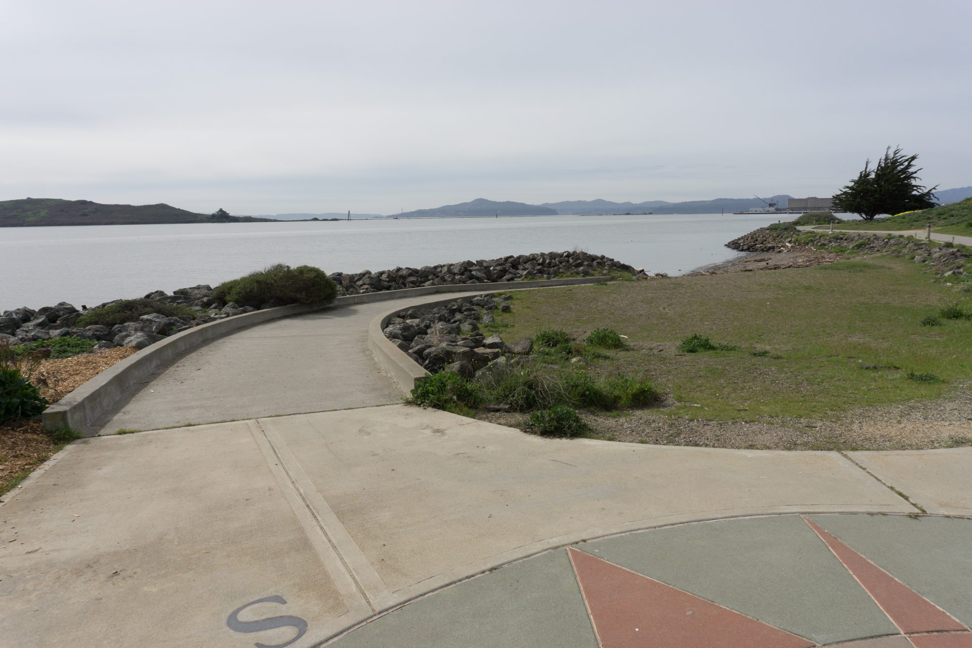 Paved path with curbs on either side curved away to right, Bay beyond.