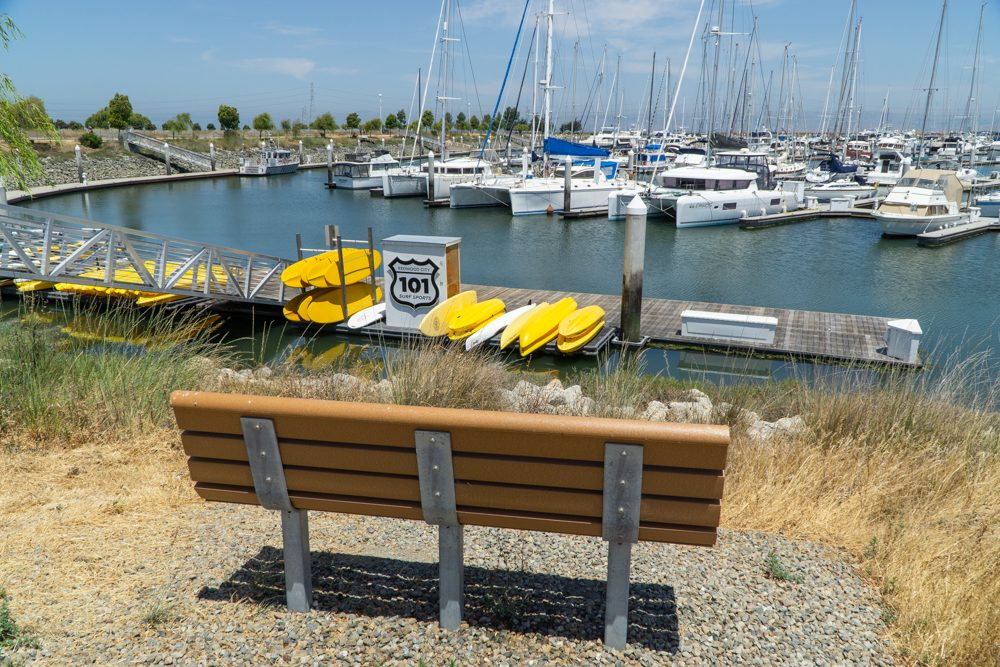 Bench in foreground, kayaks stacked on pier and sailboats beyond