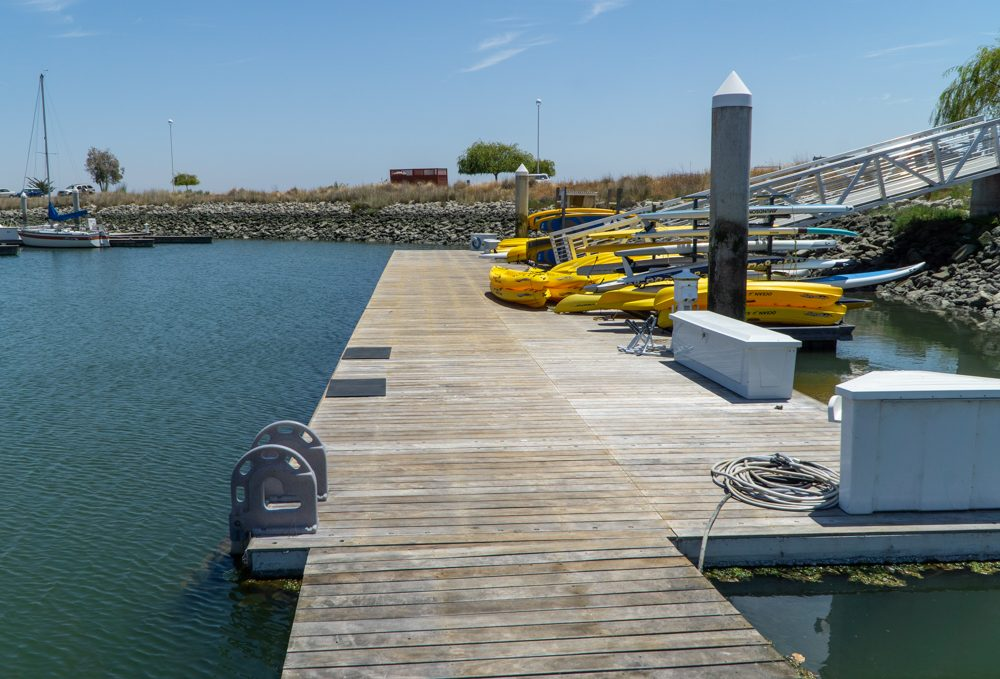 Wooden pier full of yellow kayaks and paddle boards