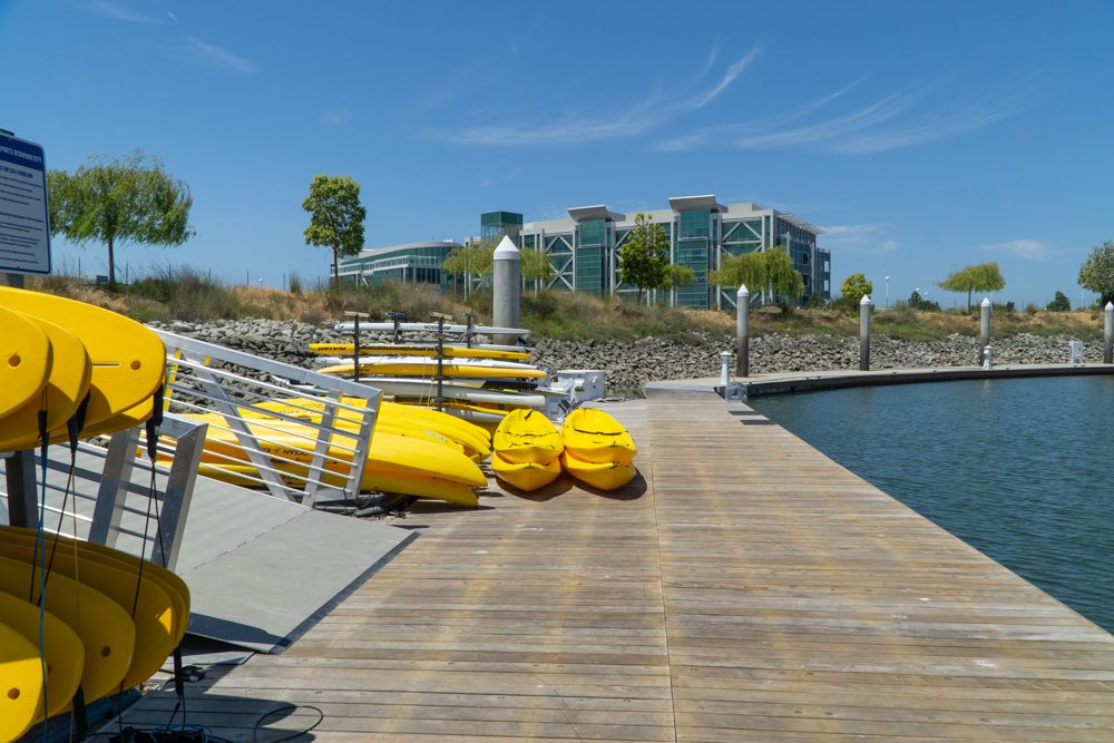 pier with water on right, racks of kayaks and boards on left