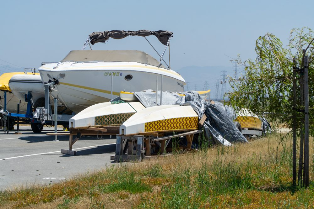 Motor boat and catamaran hauled out in parking lot