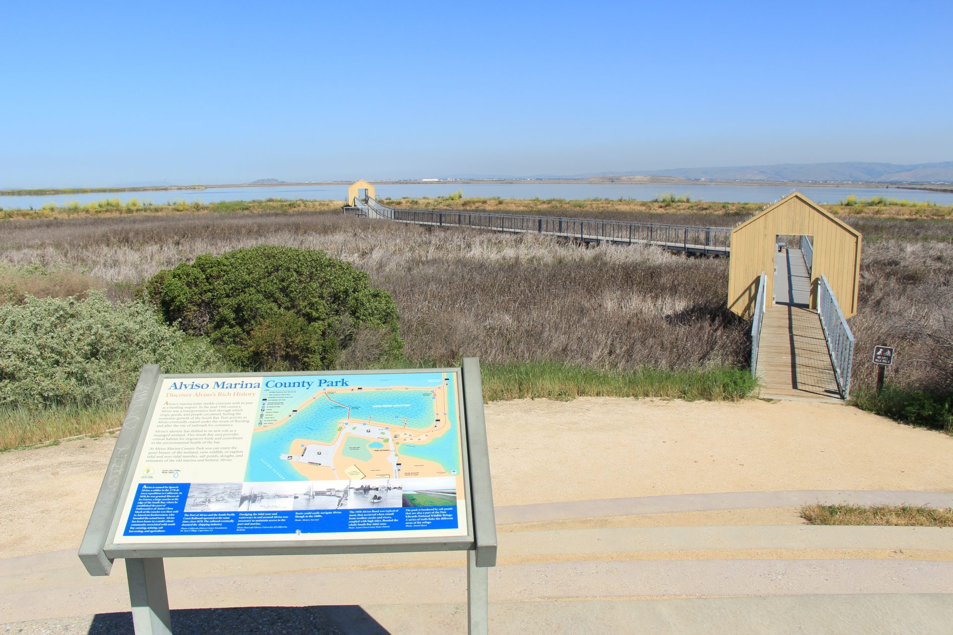 Gravel path to boardwalk extending far over marsh. Sign in foreground says,