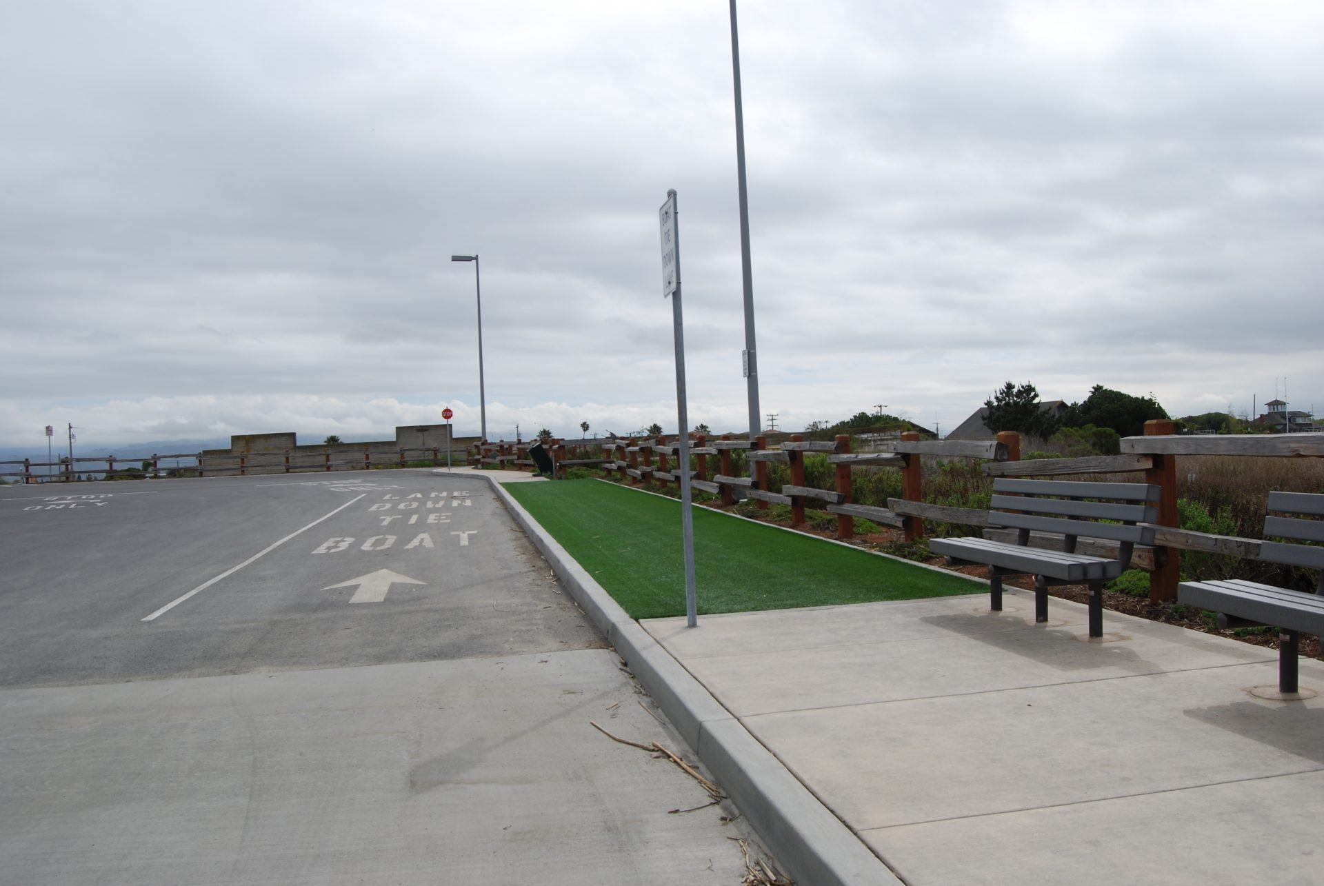 road on left, sidewalk with benches and area covered in astroturf on right