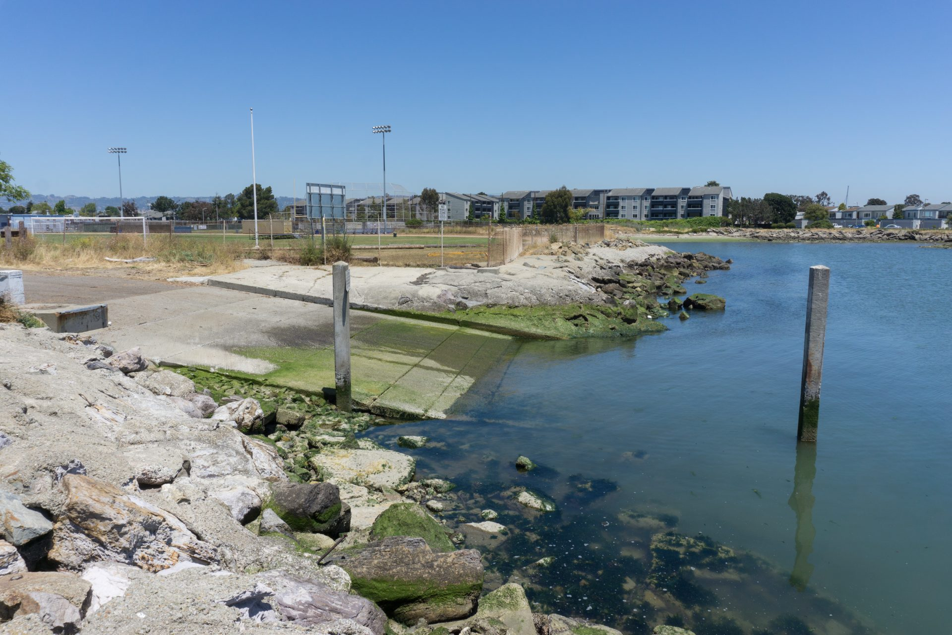 riprap foreground, then concrete boat ramp descending into water