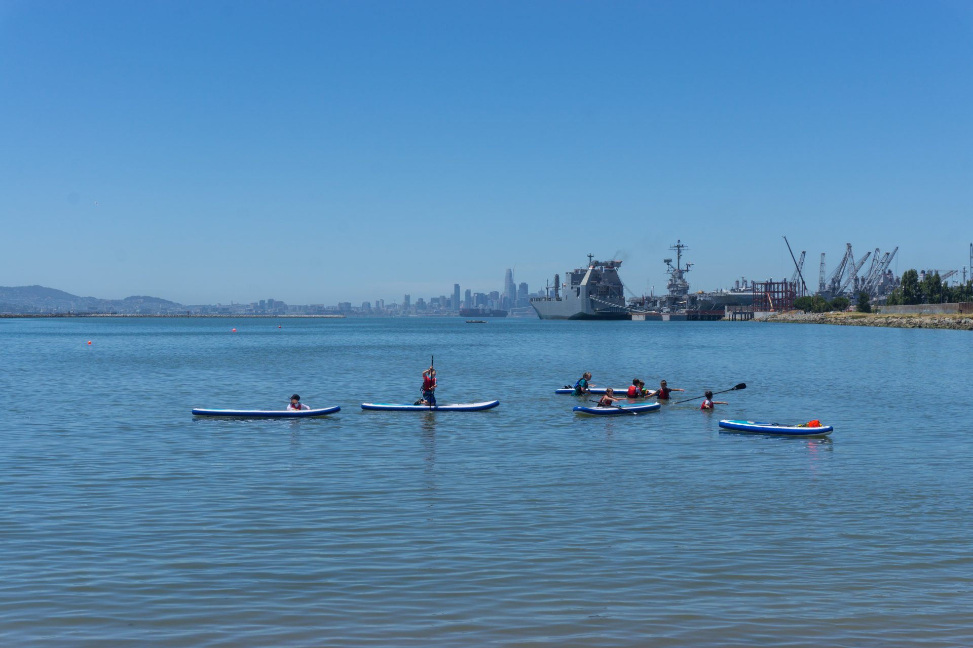 standup paddlers on still water, large ships and cranes in distance