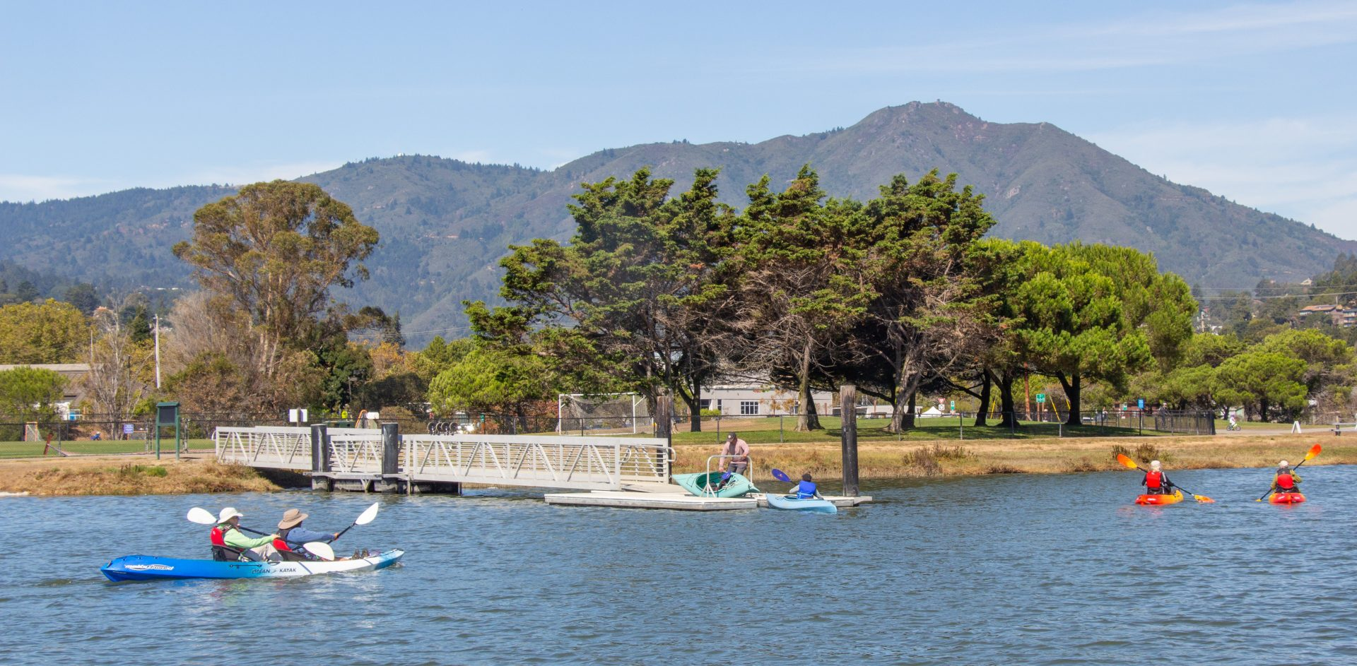 Mount Tamalpais looms over trees and pier, with kaaykers in foreground