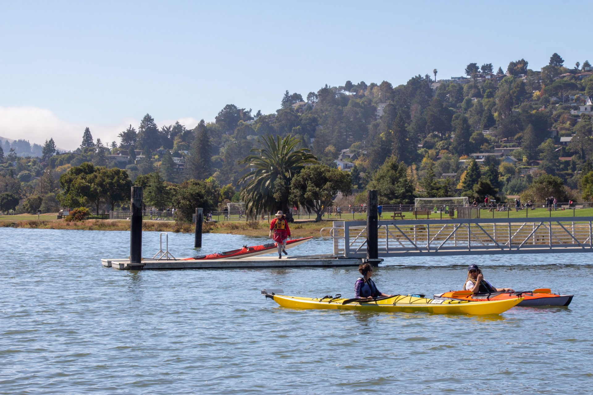 two single kayakers in foreground, third person with kayak on pier in distance