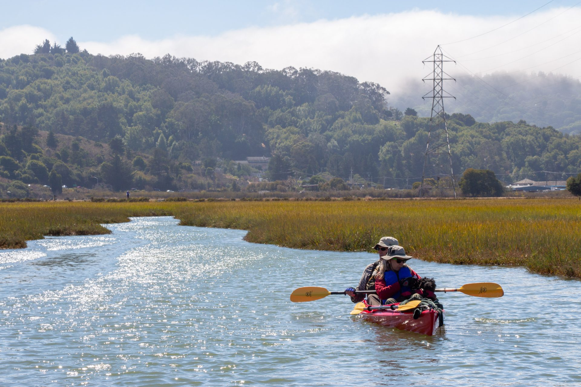 double kayaker paddling toward the camera, in a marsh channel with hills beyond