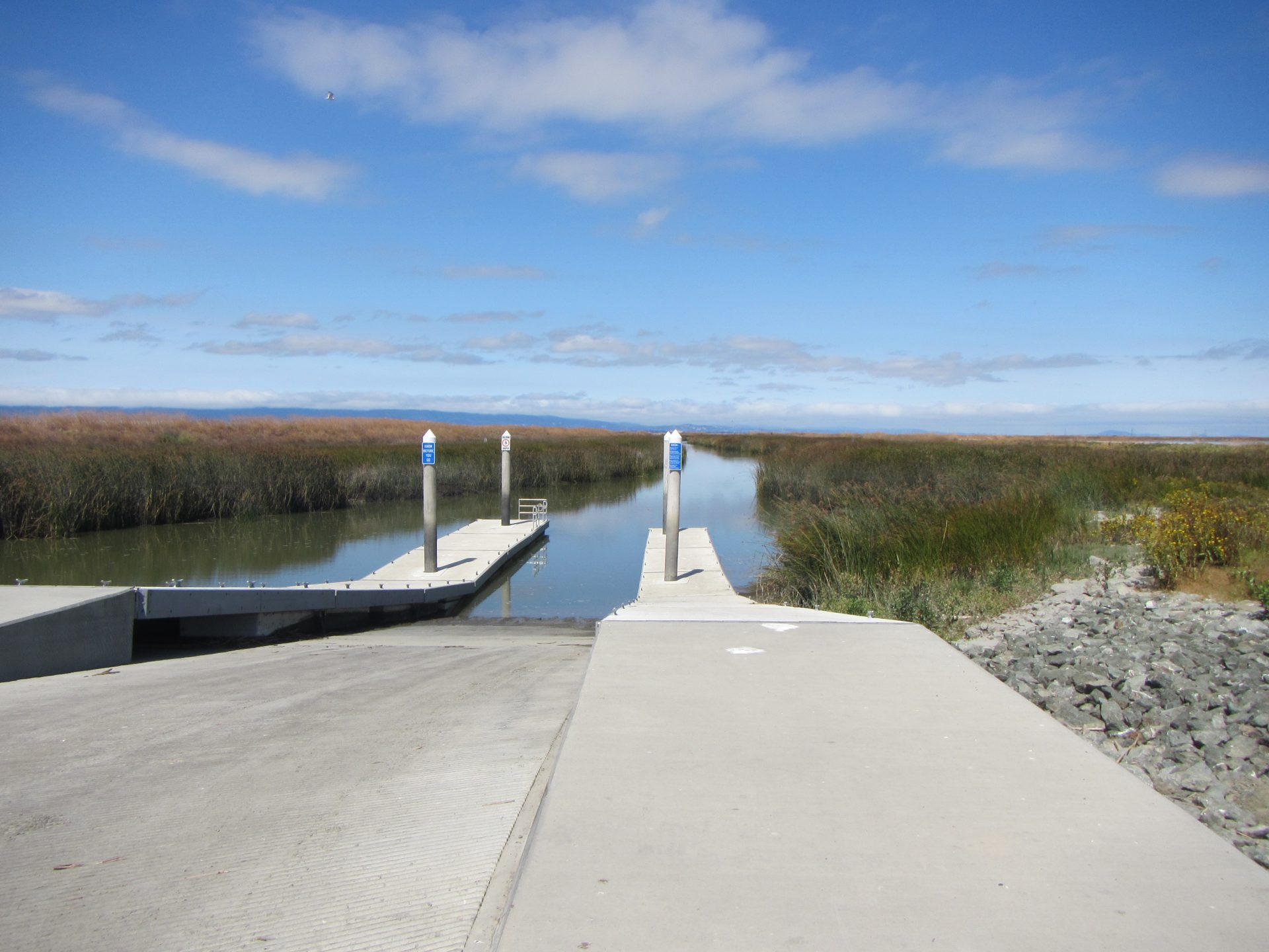 boat ramp descends into channel through marsh