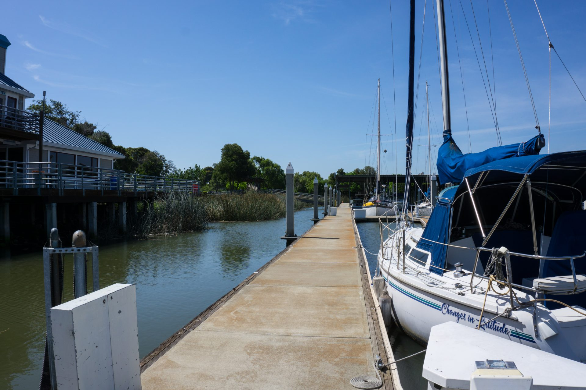 long straight concrete dock with sailboats moored on right