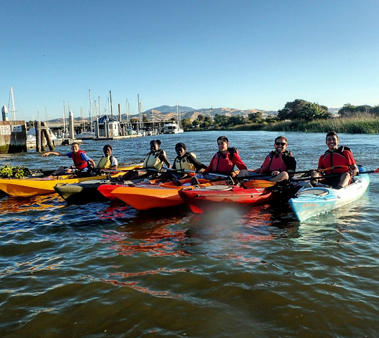 8 people in single kayaks rafted up and smiling