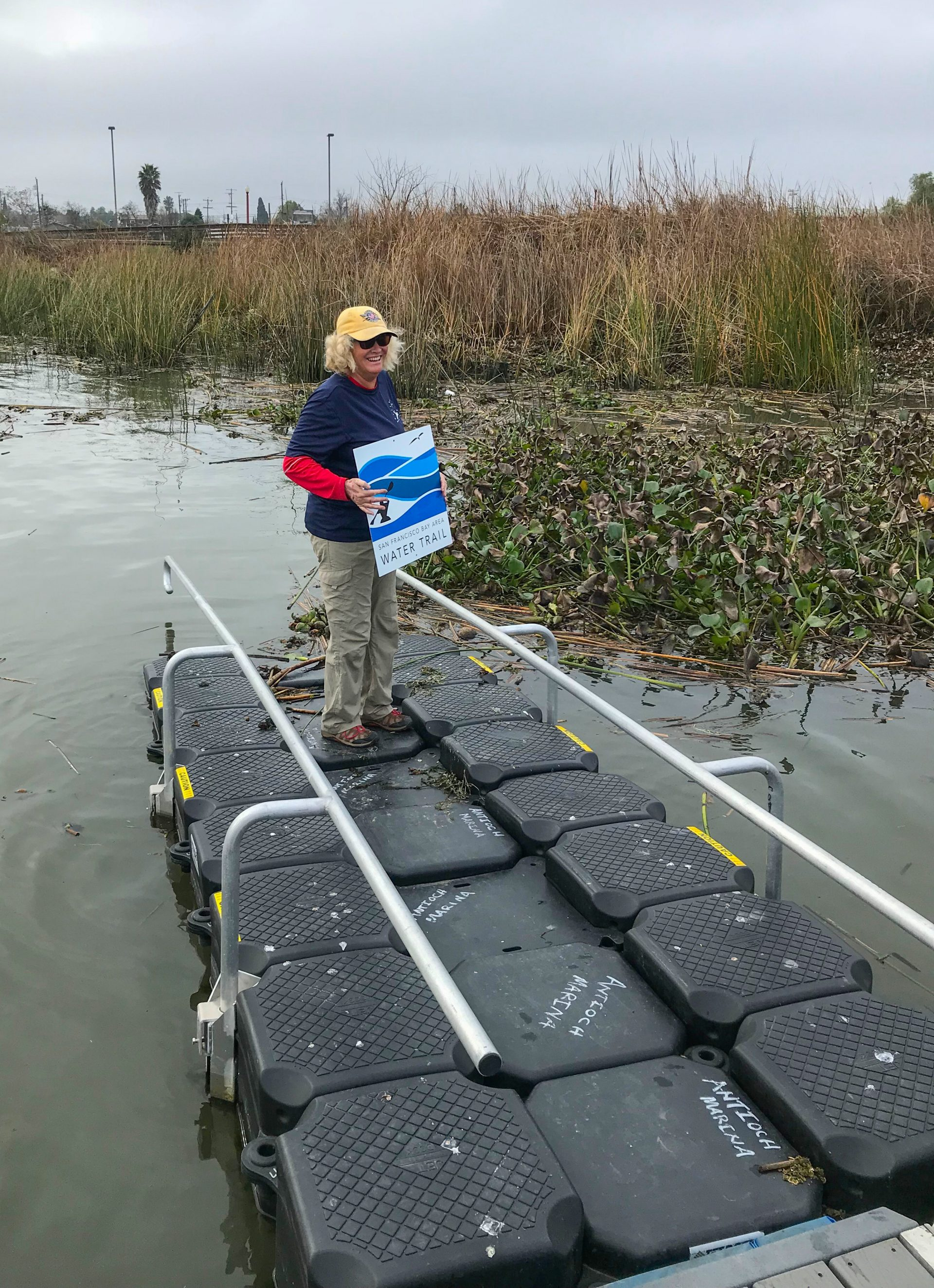 woman in blue standing on rubber dock holding Bay Water Trail sign