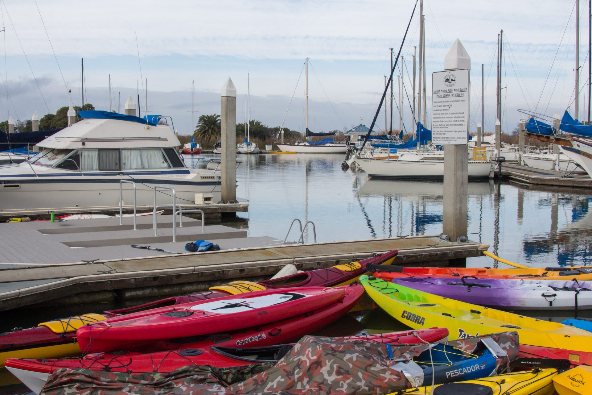 colorful kayaks in a jumble, boats docked beyond