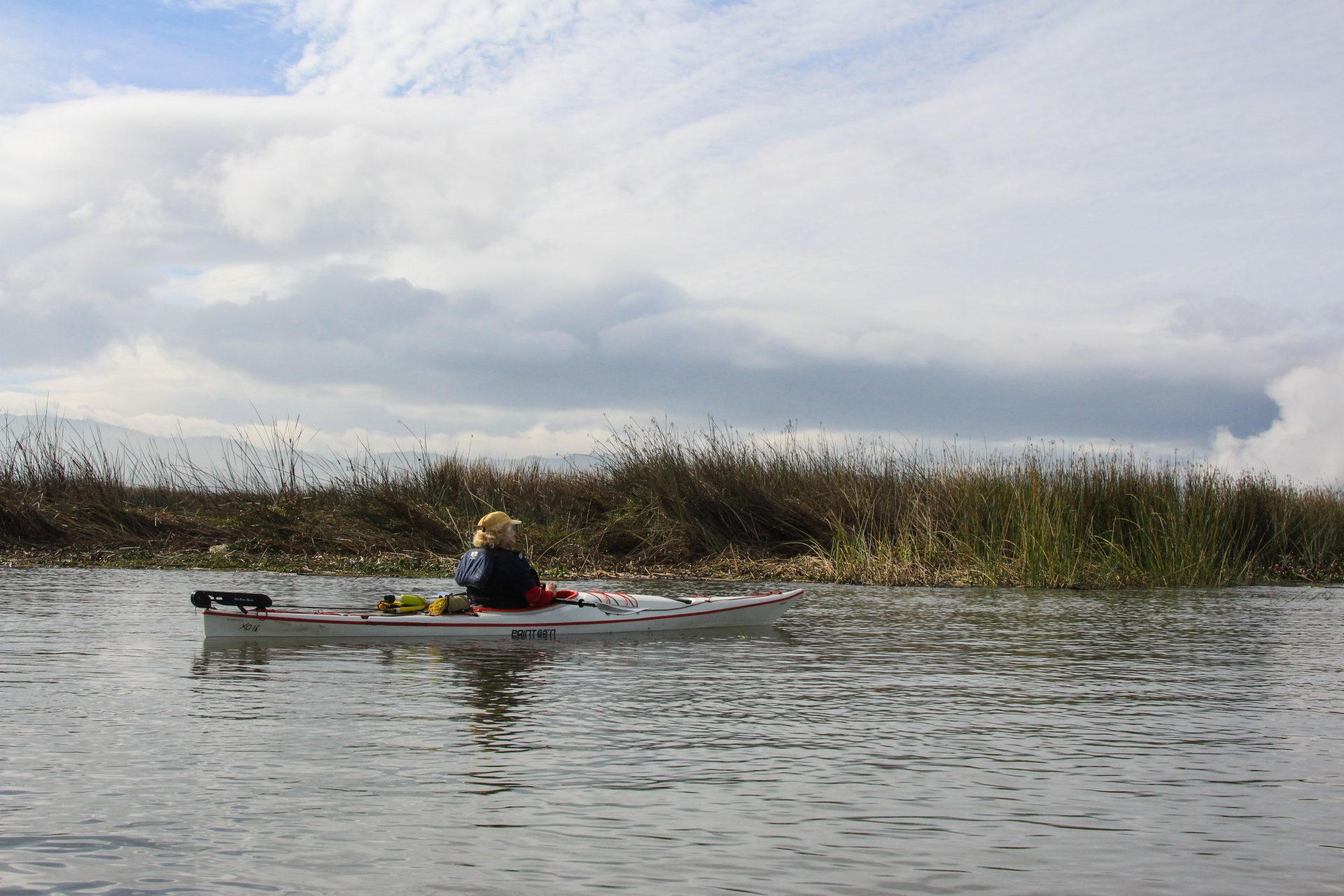 person in white ad red kayak with marsh beyond