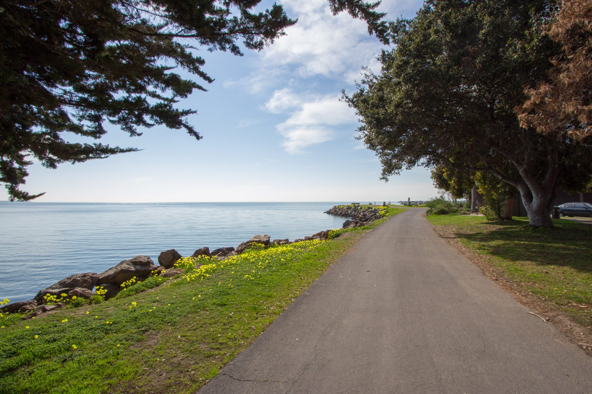 wide flat paved path extending along bay, with water on left