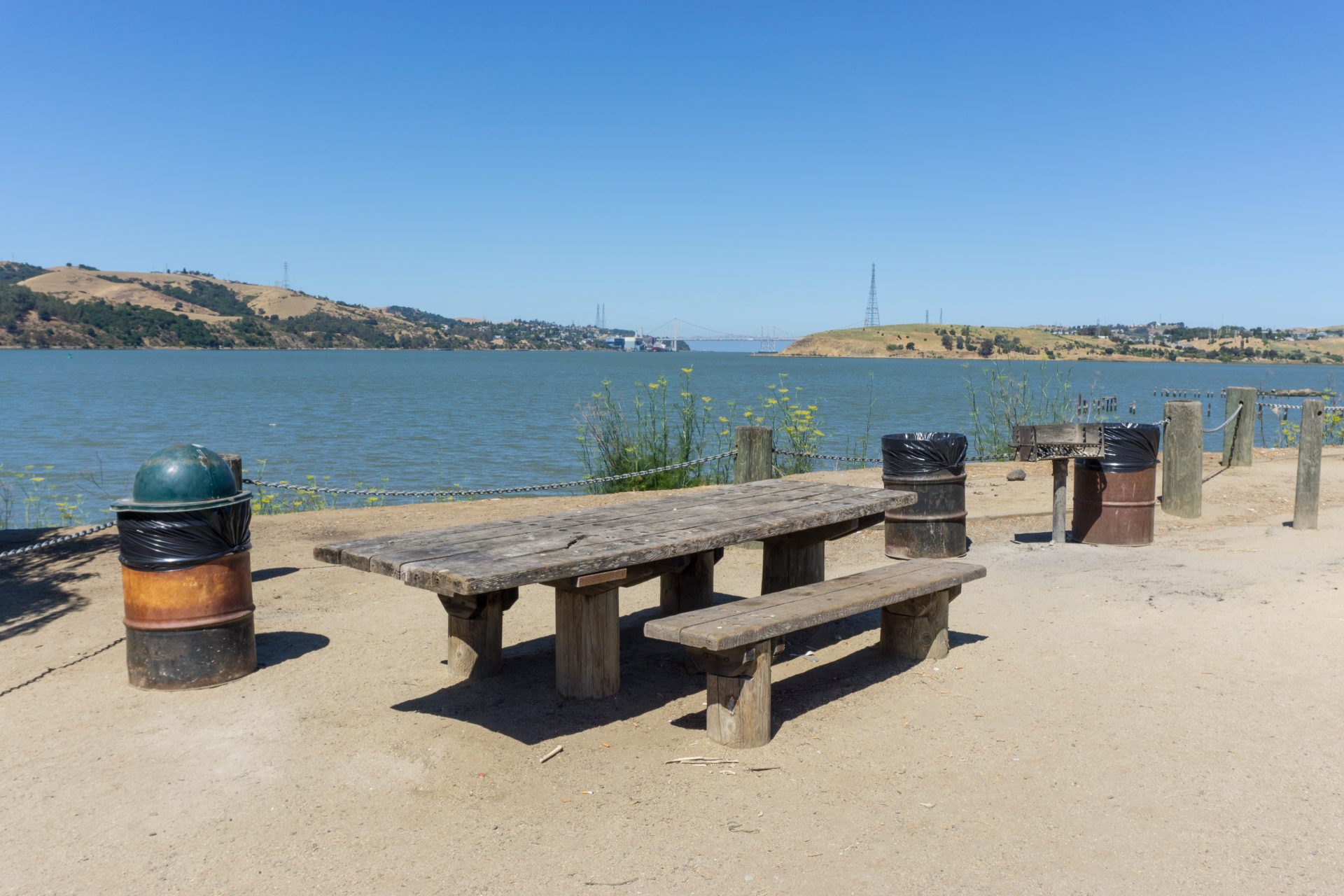 wooden picnic bench with large accessible overhang, on sand/dirt base