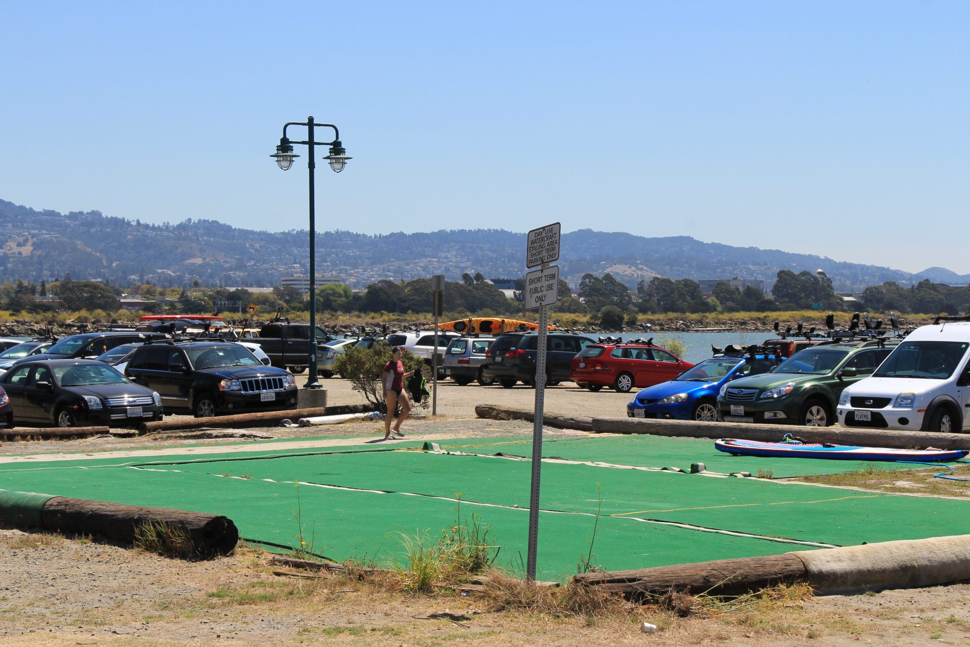 Flat area covered in green astroturf, with dirt parking lot full of cars beyond