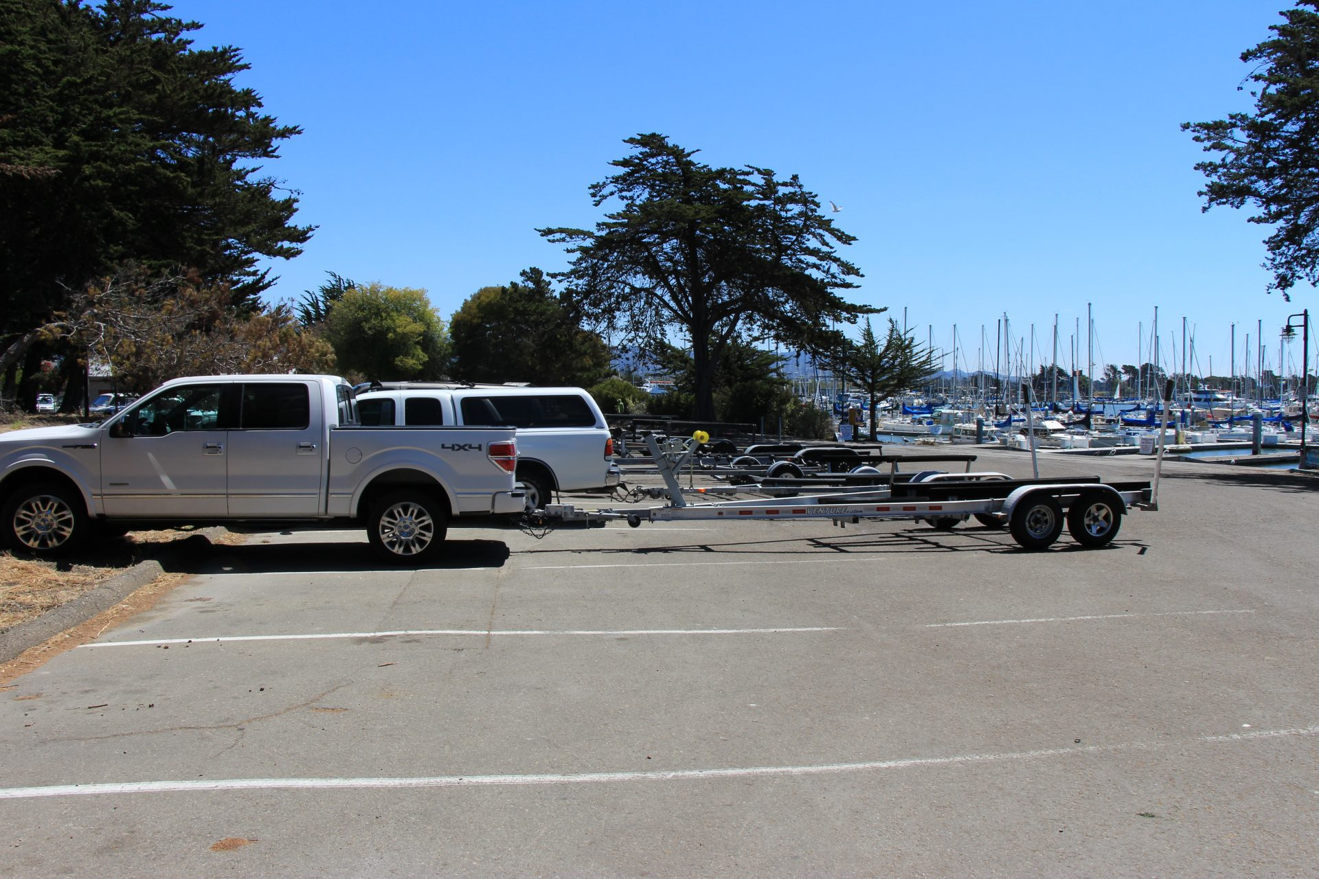 parking lot with long spots, two occupied with trucks and empty boat trailers