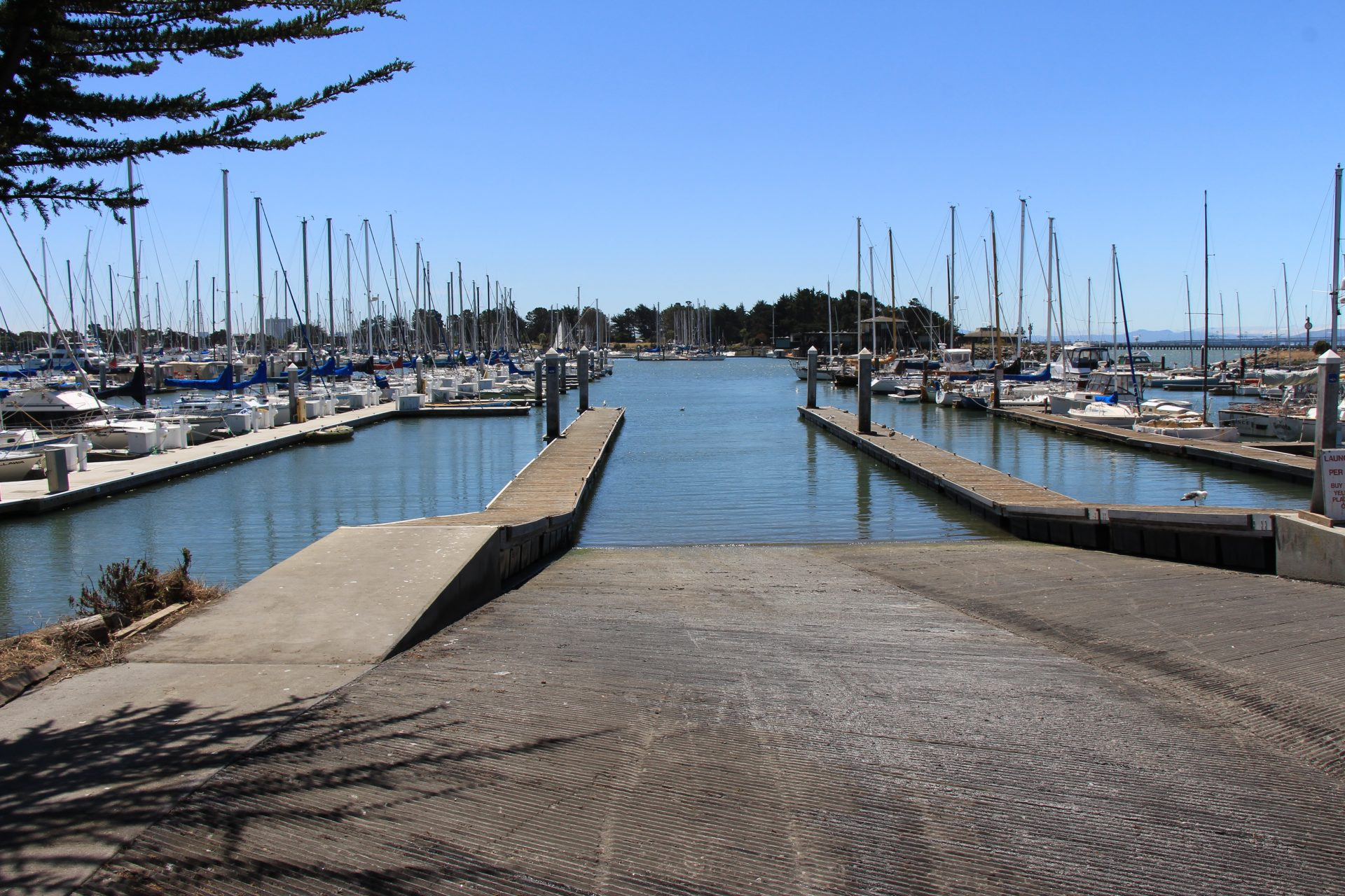 Wide boat ramp descending into water, with sailboats moored all aorund