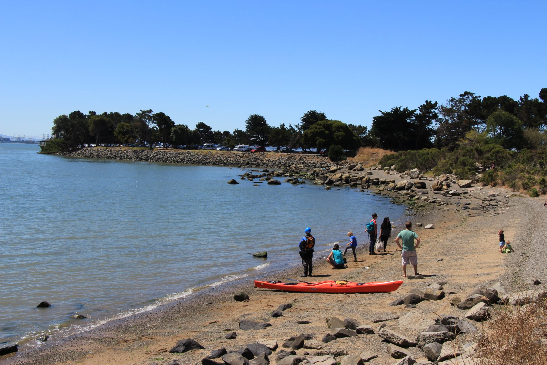 Single red kayak with 5 adults and 3 children milling around on rocky beach