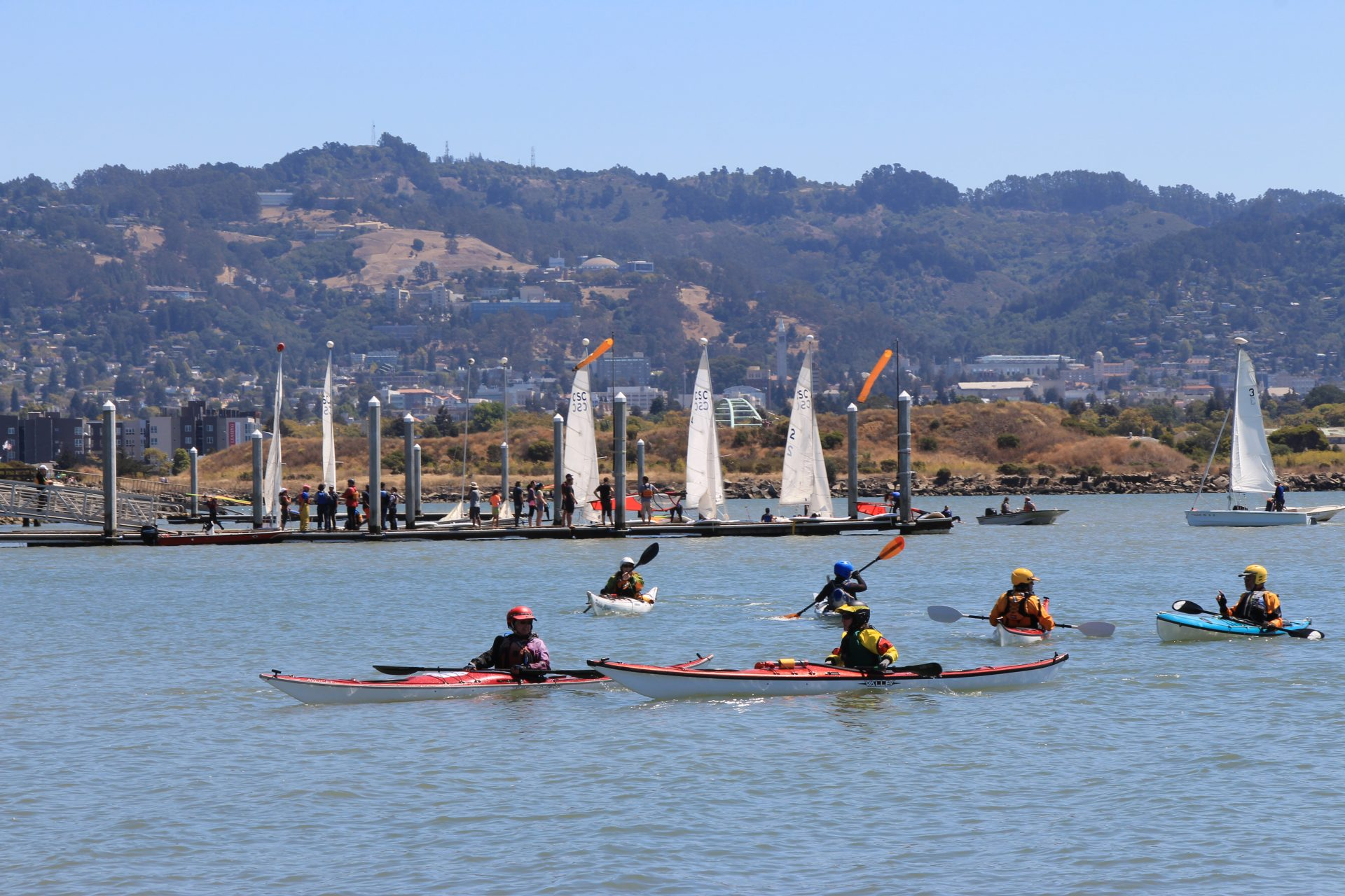 Six kayakers paddling on blue water, sailboats behind and east Bay hills in distance